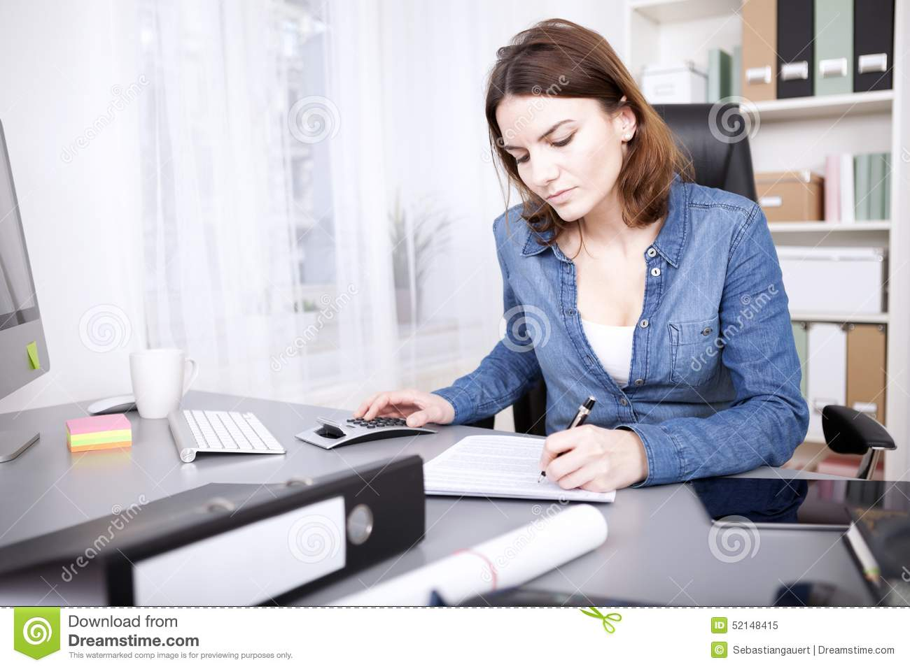 Businesswoman Sitting In Office Reception Area Looking At