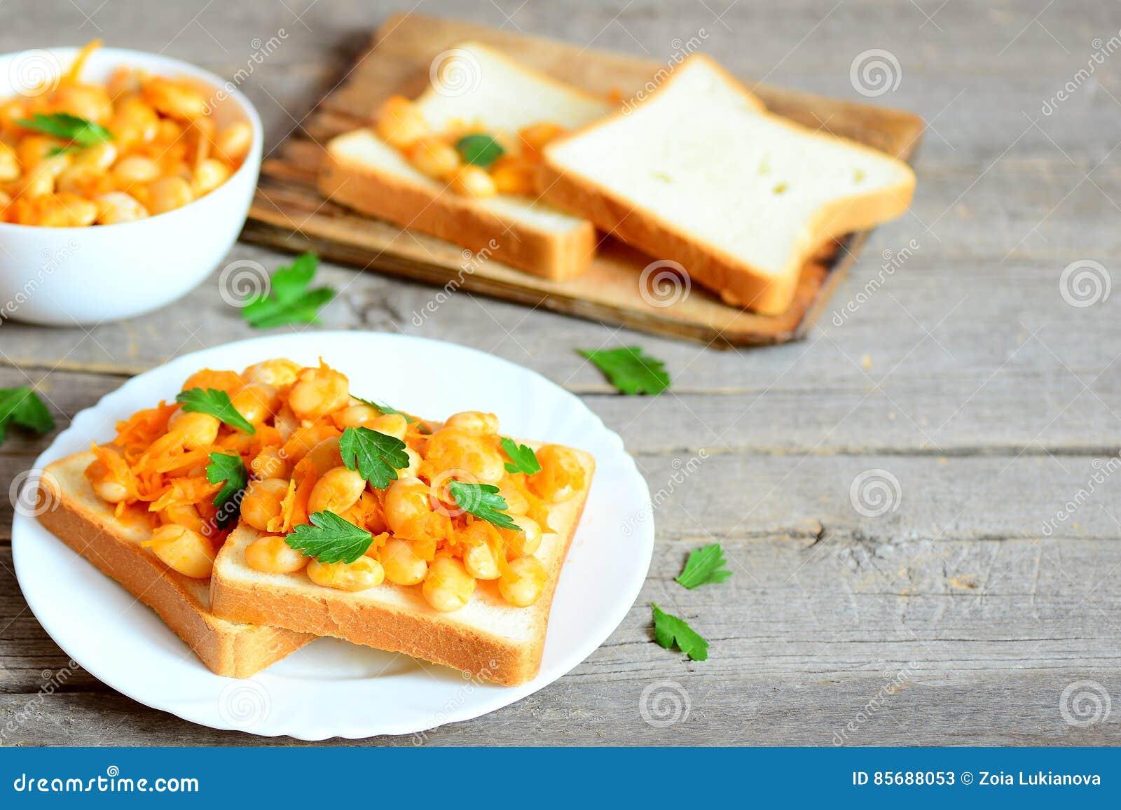 Haricots cuits au four avec des légumes sur le pain blanc et de plat Haricots blancs cuits au four dans une cuvette, tranches de