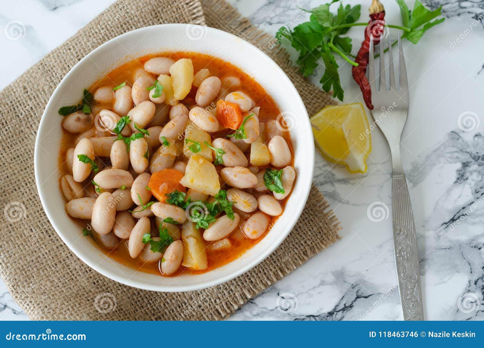 Haricots nains rouges en sauce tomate avec la carotte dans une cuvette blanche,