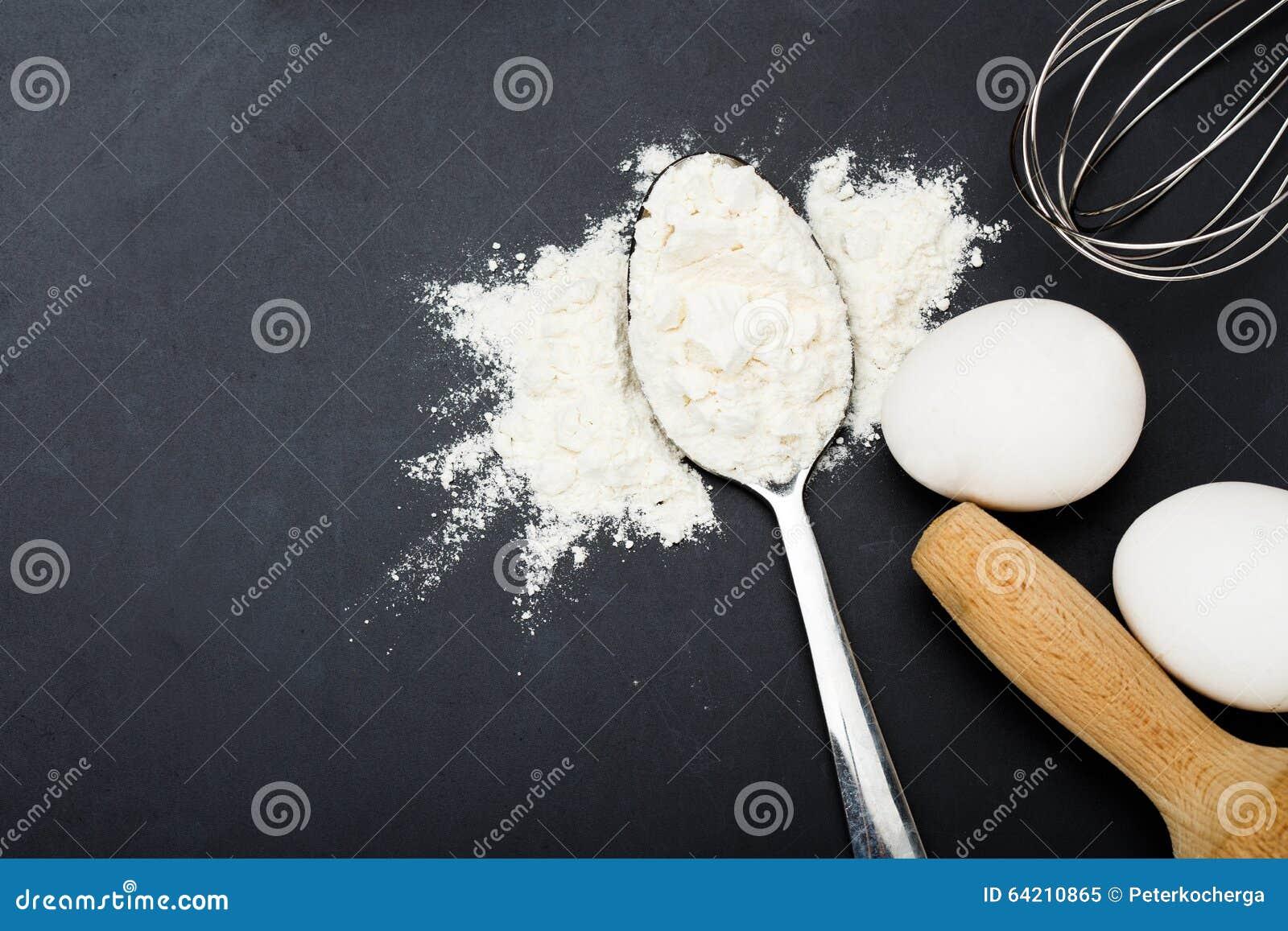 Harina blanca y huevos en la tabla negra