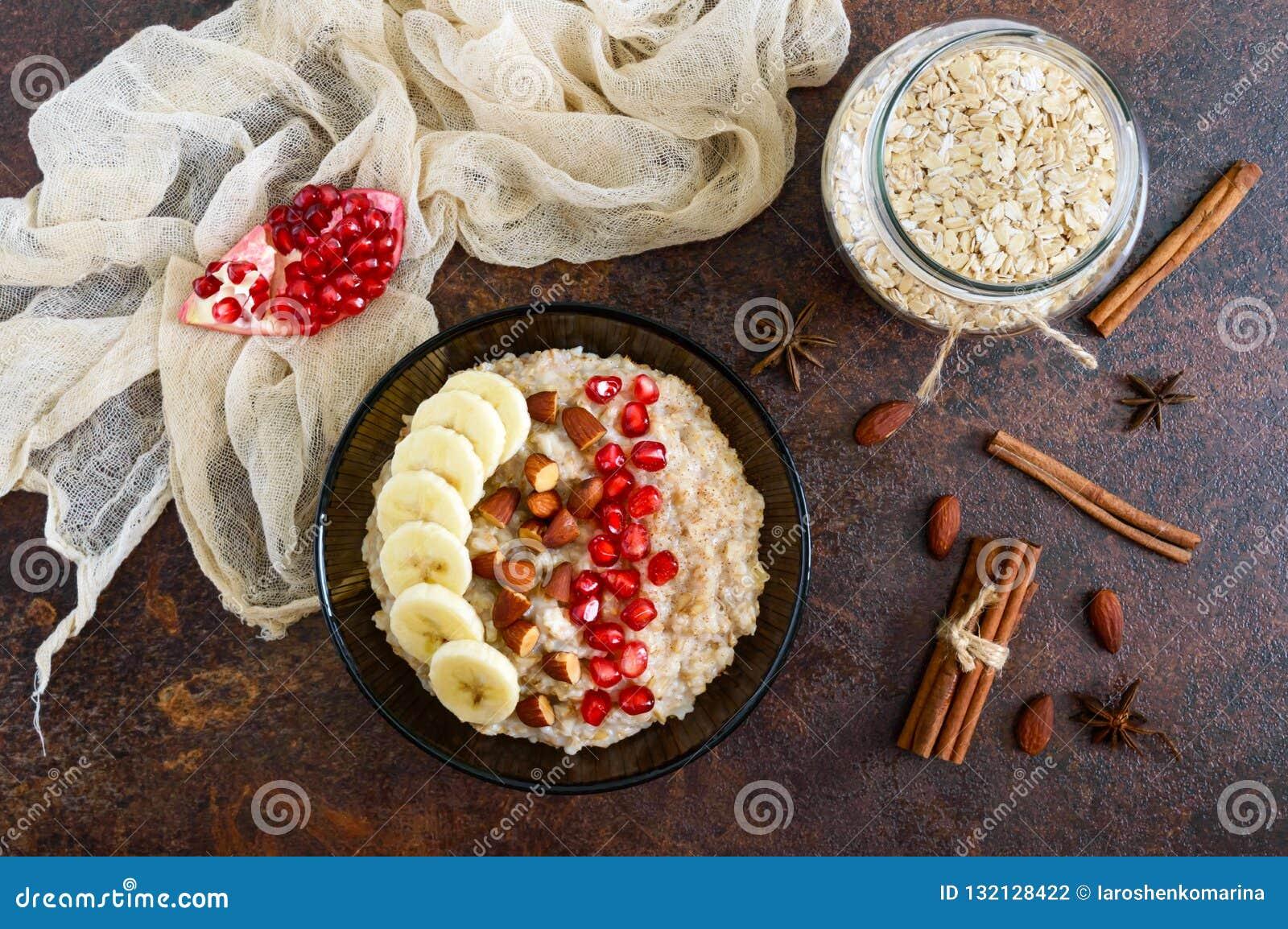 Harina de avena deliciosa y sana con el plátano, las semillas de la granada, la almendra y el canela