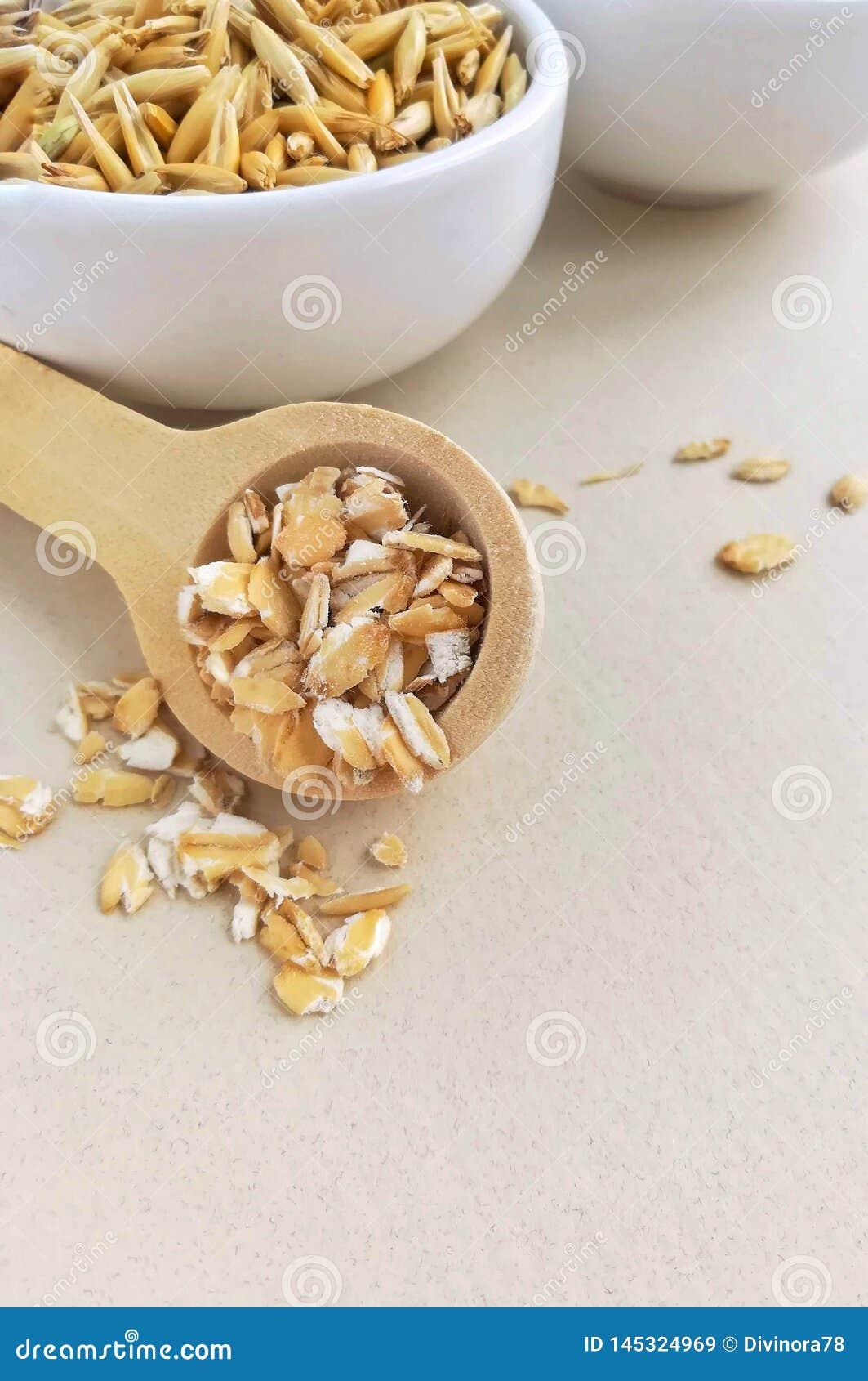 Harina de avena en una cuchara de madera y granos enteros de la avena