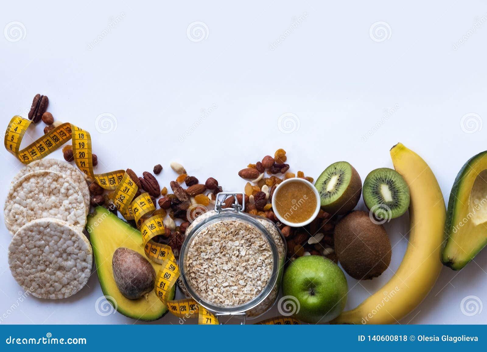 Harina de avena sana del desayuno con las pasas y las nueces Almendras, miel, manzana, aguacate, plátano en el fondo blanco de la