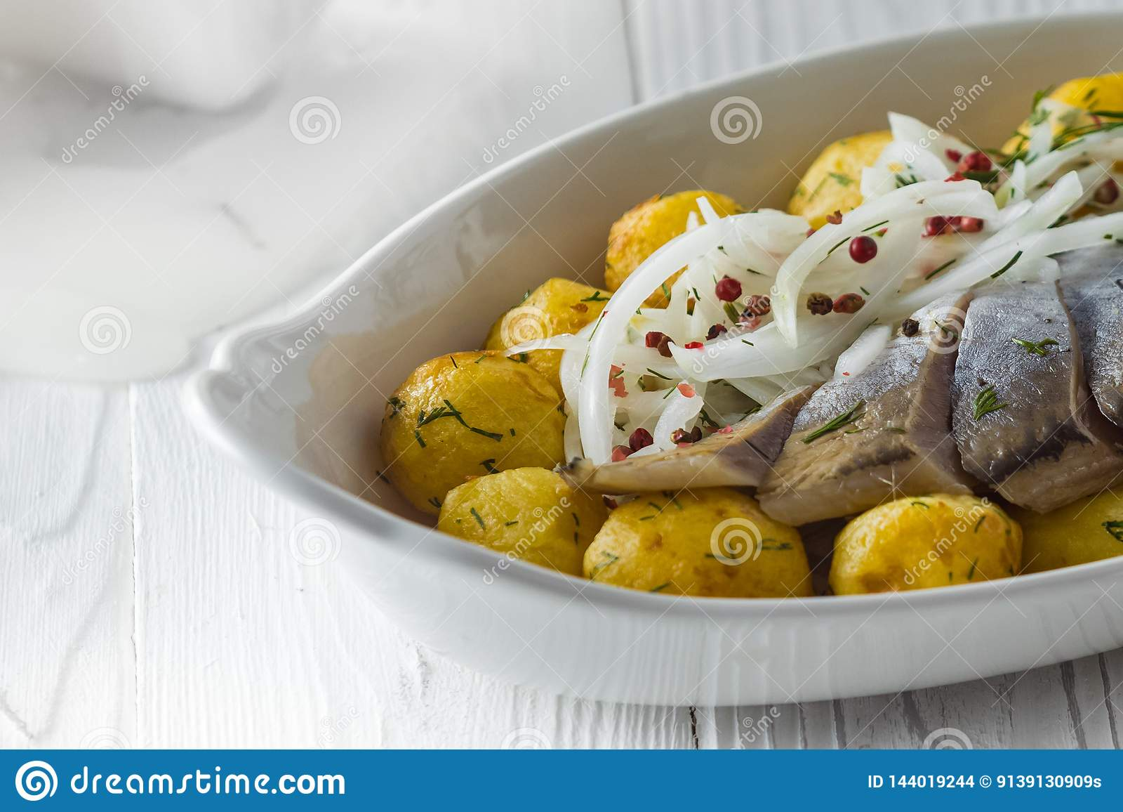Haringen met gebraden aardappels en ui op een plaat