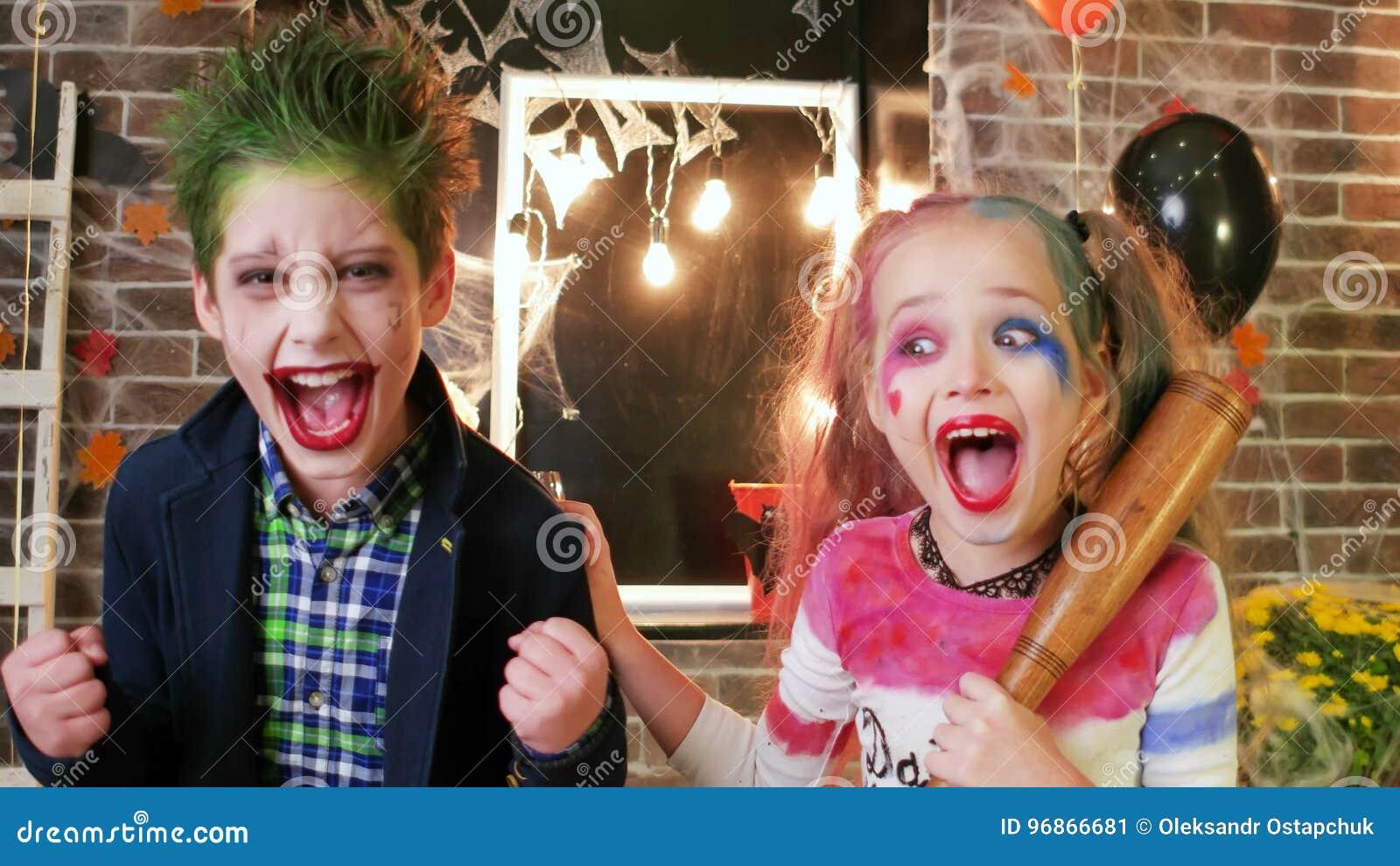 Harley Quinn et joker criant, enfants ayant l amusement à la partie de  Halloween, caractère fou, maquillage fantasmagorique.