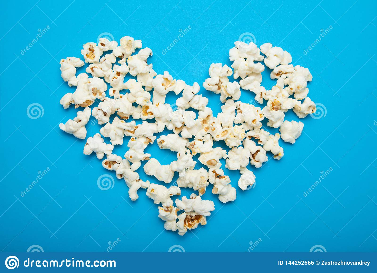Hart dat van heerlijke popcorn op een blauwe achtergrond wordt gemaakt