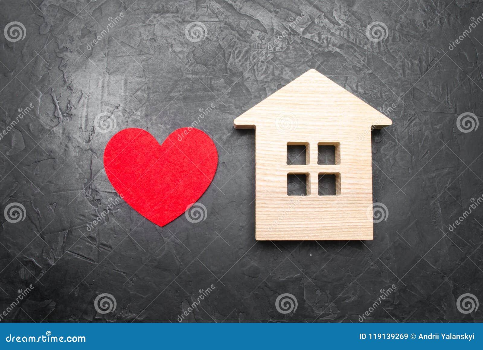 Hart en blokhuis op een grijze concrete achtergrond Het concept een liefdenest, het onderzoek naar nieuwe betaalbare huisvesting