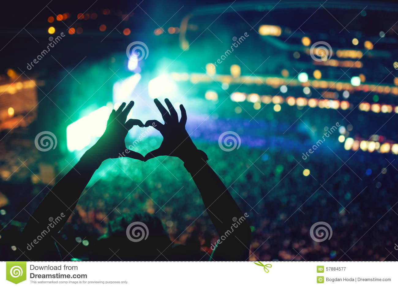 Hart gevormde handen bij overleg, houdend van de kunstenaar en van het festival Muziekoverleg met lichten en silhouet van mens he