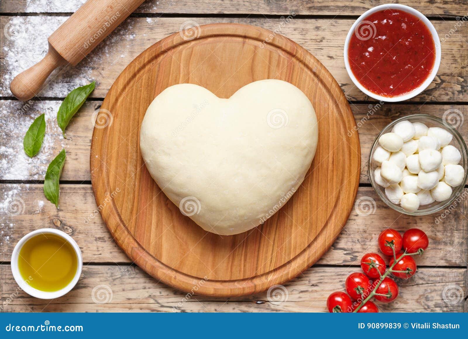 Hart gevormde pizza kokende ingrediënten Deeg, mozarella, tomaten, basilicum, olijfolie, kruiden Het werk met het deeg bovenkant