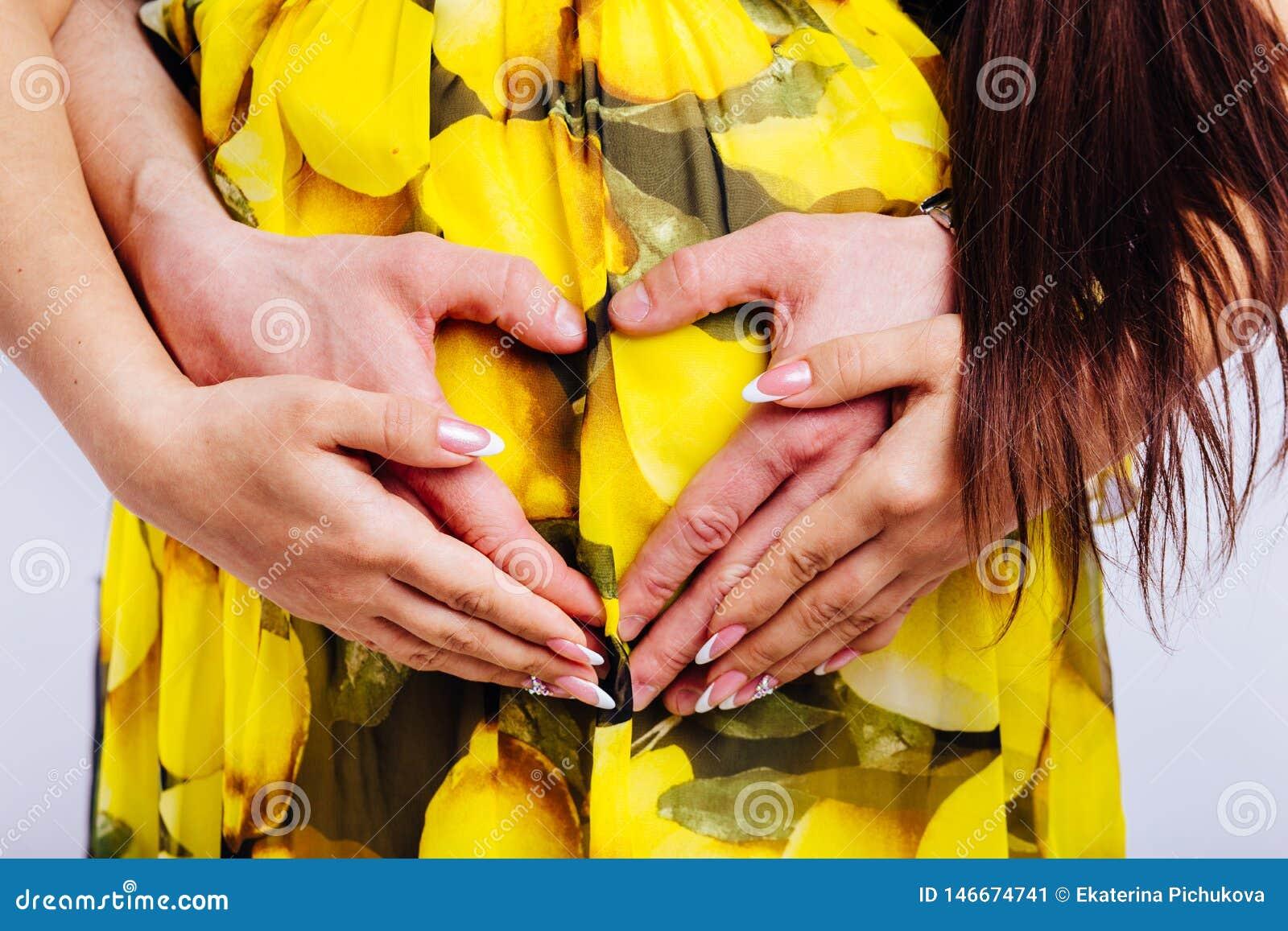 Hart van de handen op de buik van een zwangere vrouw worden gevouwen die