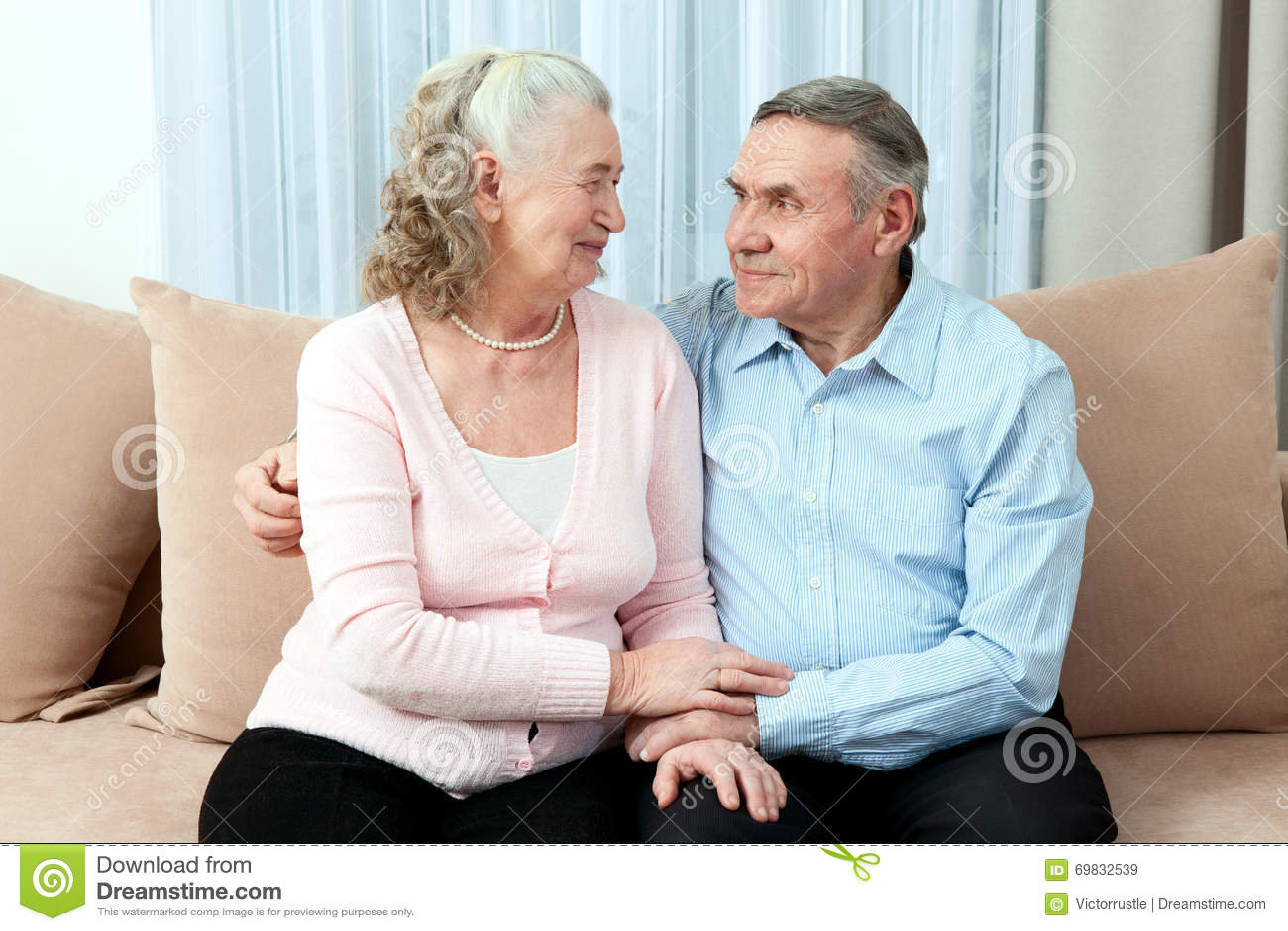 Hartelijk bejaard paar met mooie richtende vriendschappelijke glimlachen die samen in een dichte greep in hun woonkamer stellen P