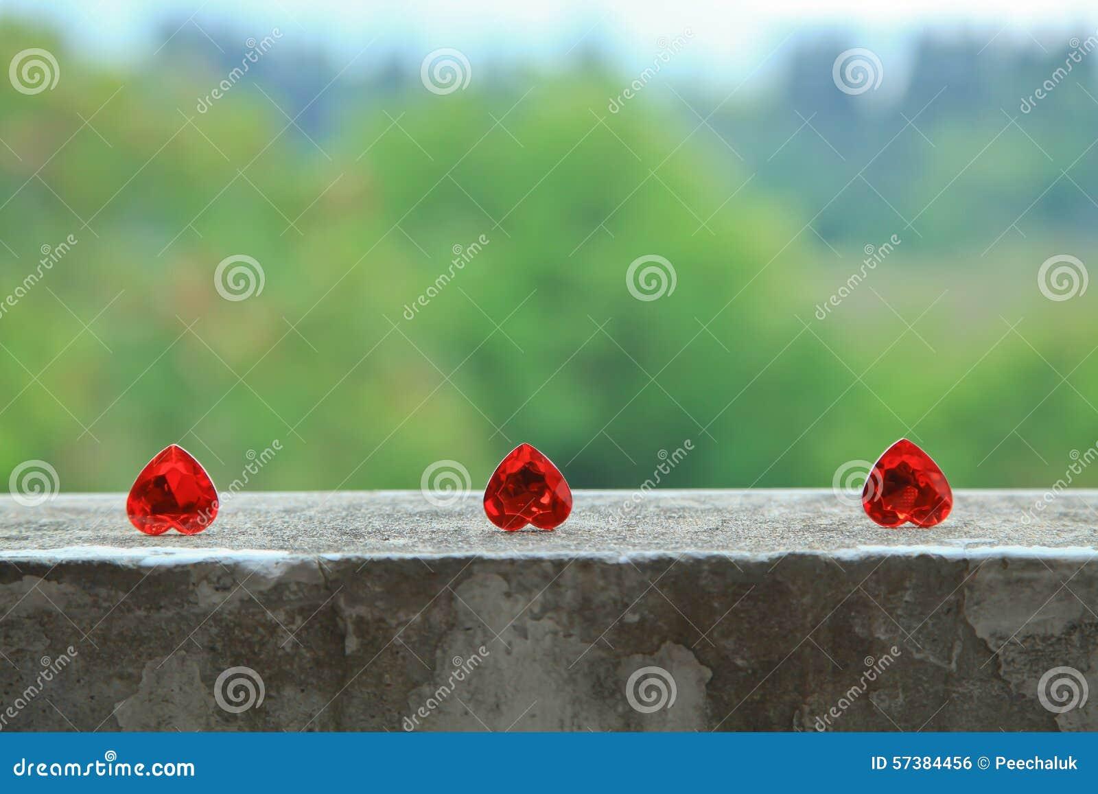 3 harten op het cement floorhearts op de cementvloer de groene achtergrond
