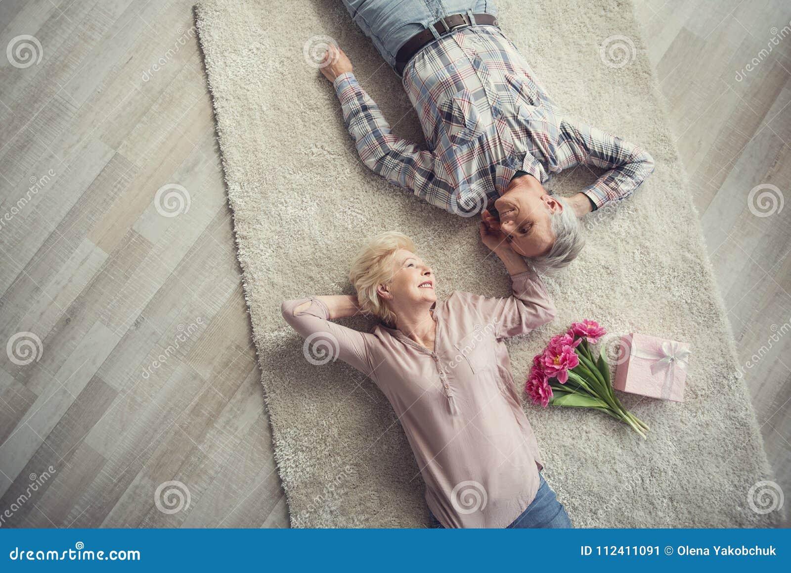 Hartstochtelijk rijp paar die op de vloer rusten