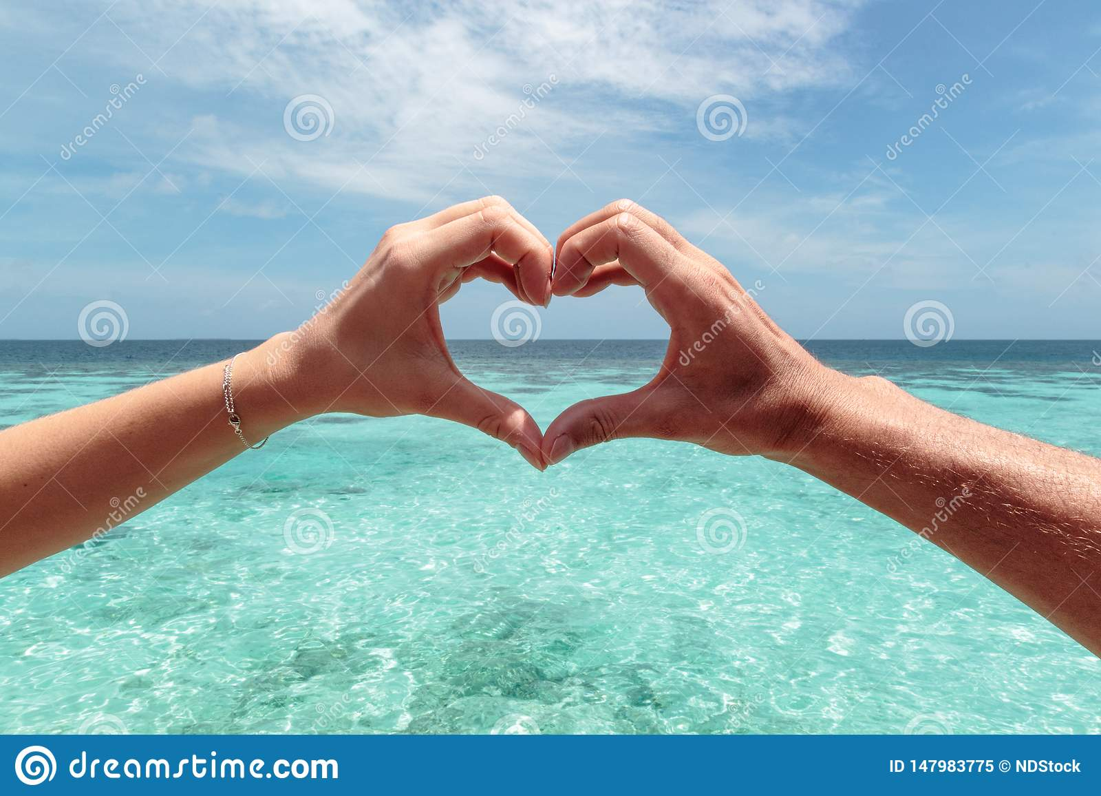 Hartvorm met een mannelijke en vrouwelijke hand Duidelijk blauw water als achtergrond Vrijheid in paradijsconcept