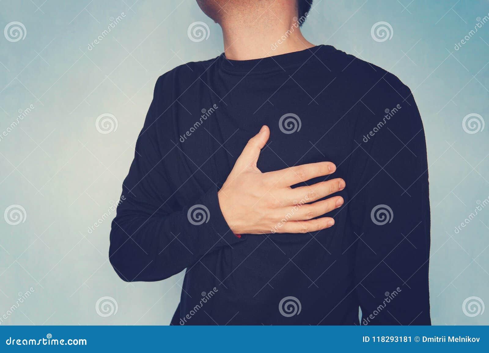 Hartzeer, mens die aan borstpijn lijden, die hartaanval of pijnlijke klemmen, die op borst met pijnlijke uitdrukking hebben drukk
