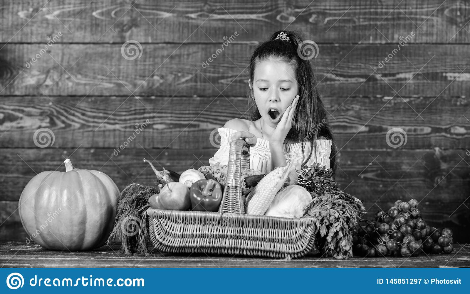 Harvest festival concept. Girl kid rustic style farmers market with fall harvest. Child cheerful celebrate harvest