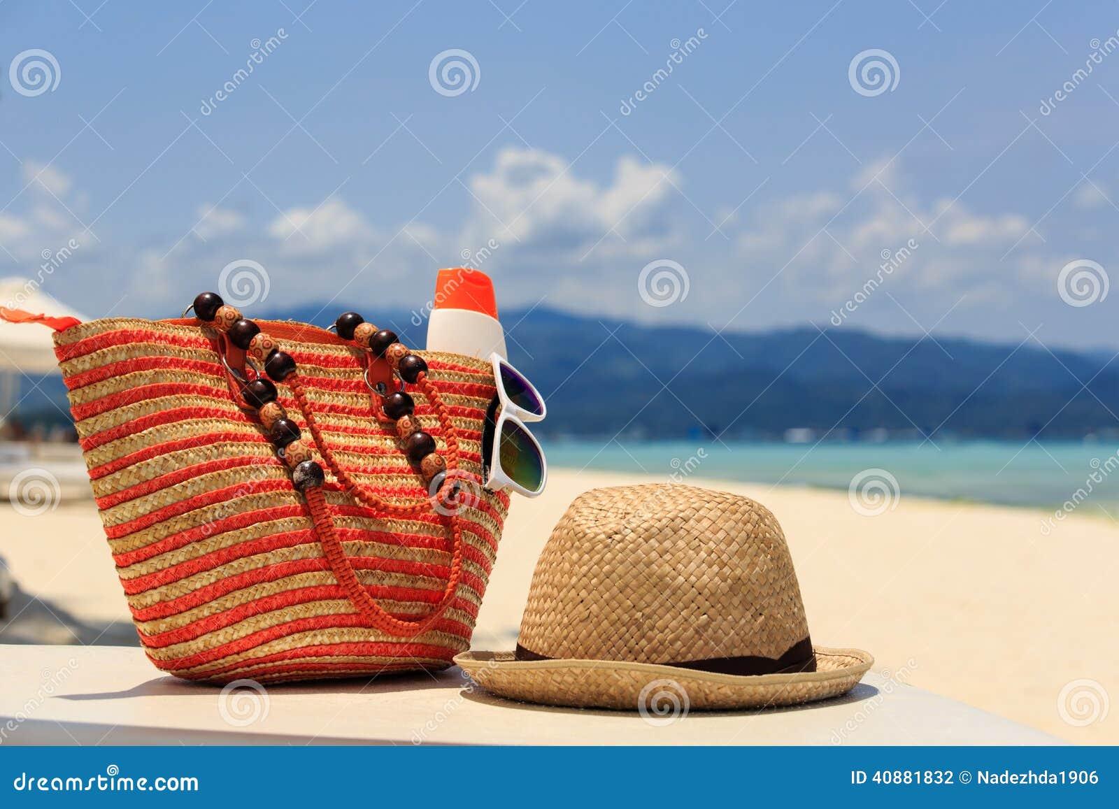 Hat, bag, sun glasses and flip flops on tropical beach