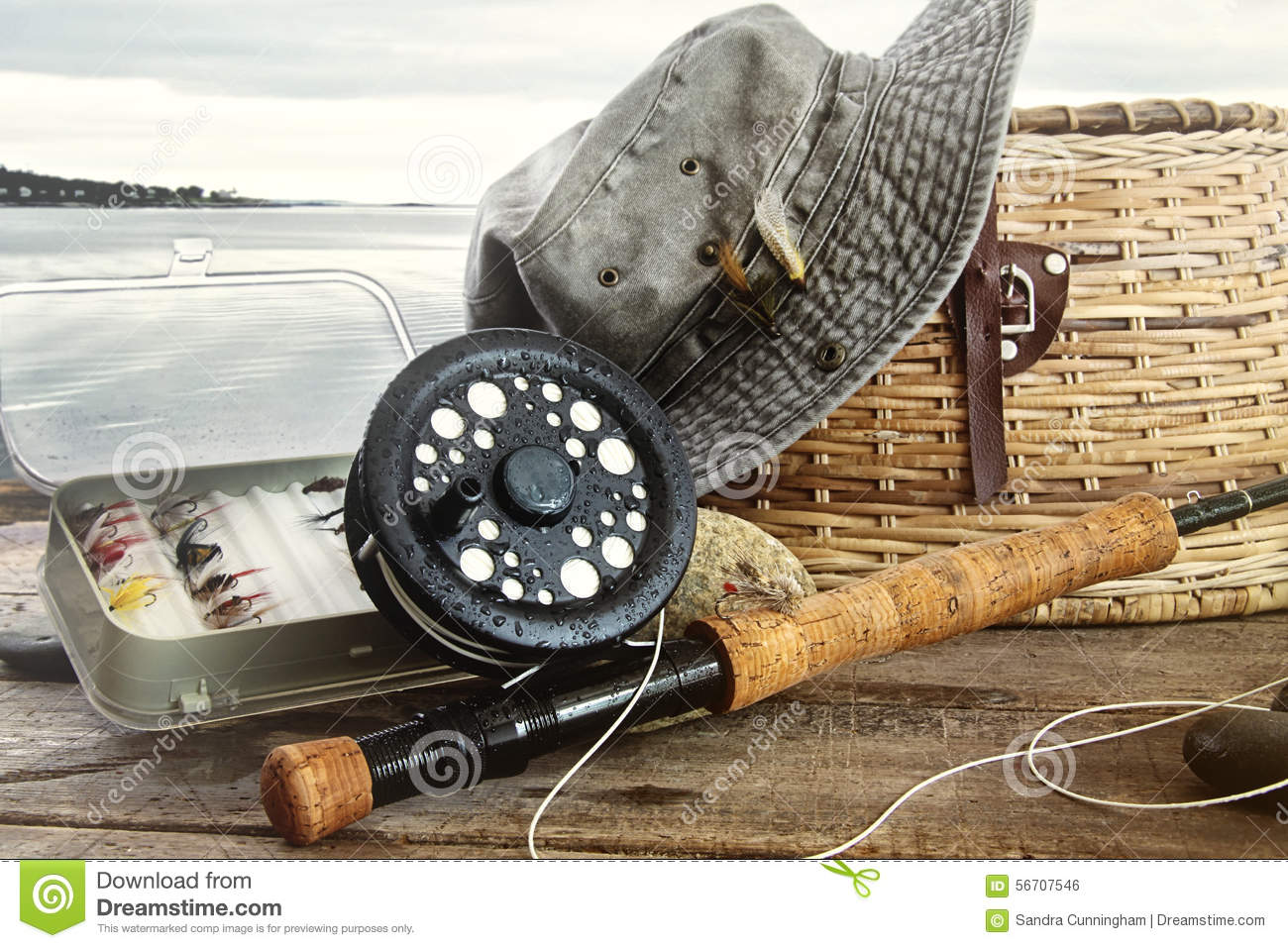 hat and fly fishing gear on table near the water stock