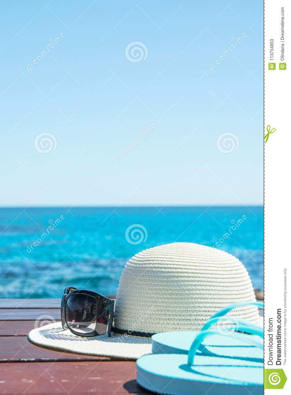 Hat Sunglasses Slippers on Blue Sky and Turquoise Sea Background. Summer Vacation Travel Relaxation. Idyllic Seascape View
