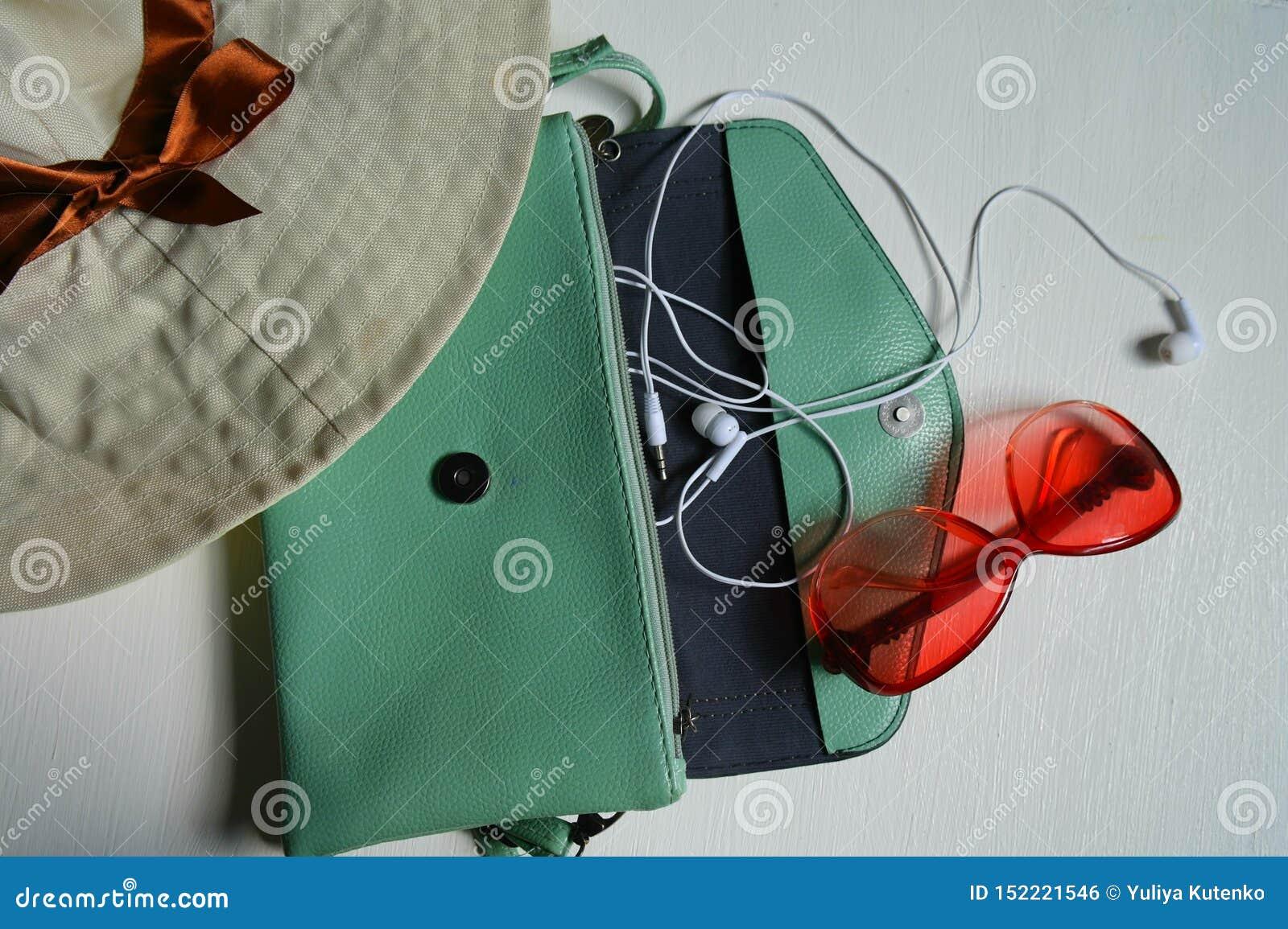 Hatt handväska, hörlurar, exponeringsglas på vit bakgrund