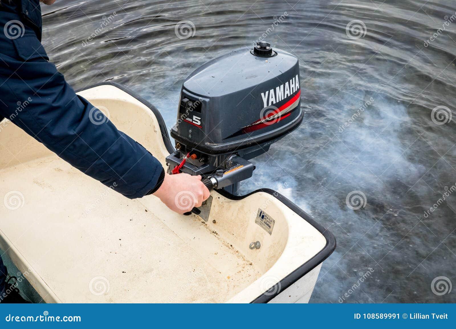 Haugesund, Noorwegen - januray 10, 2018: Mens die een buitenboordmotor van Yamaha op een plastic boot, uitlaatrook van beginnen
