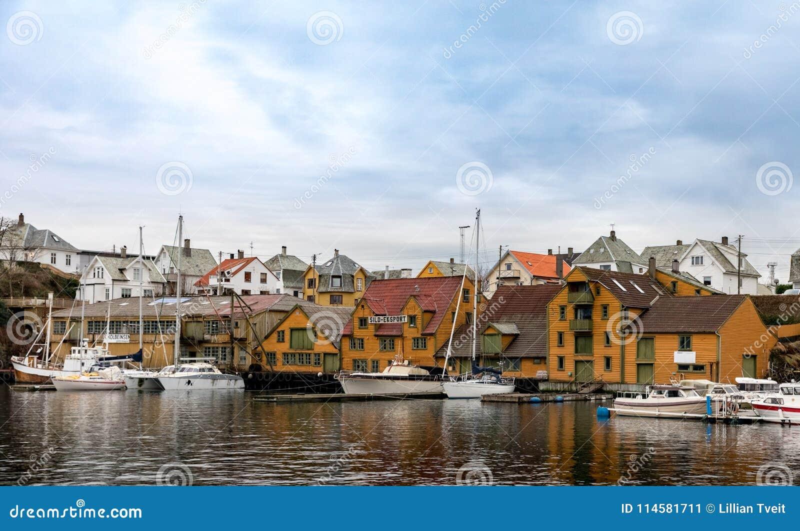 Haugesund Norwegia, Styczeń, - 9, 2018: Starzy drewniani domy na wyspy Risoy, łodzi i połowu przemysłu budynkach, Sild