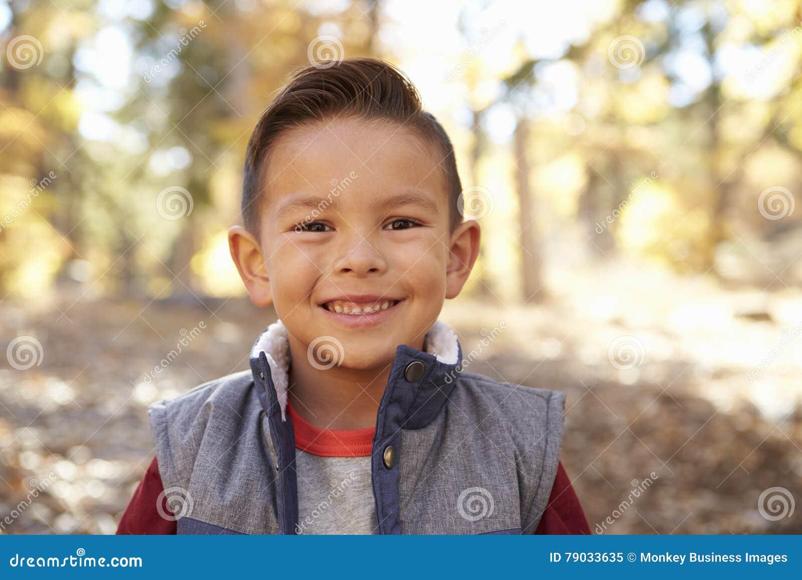 Haupt- und Schulterporträt eines hispanischen Jungen in einem Wald