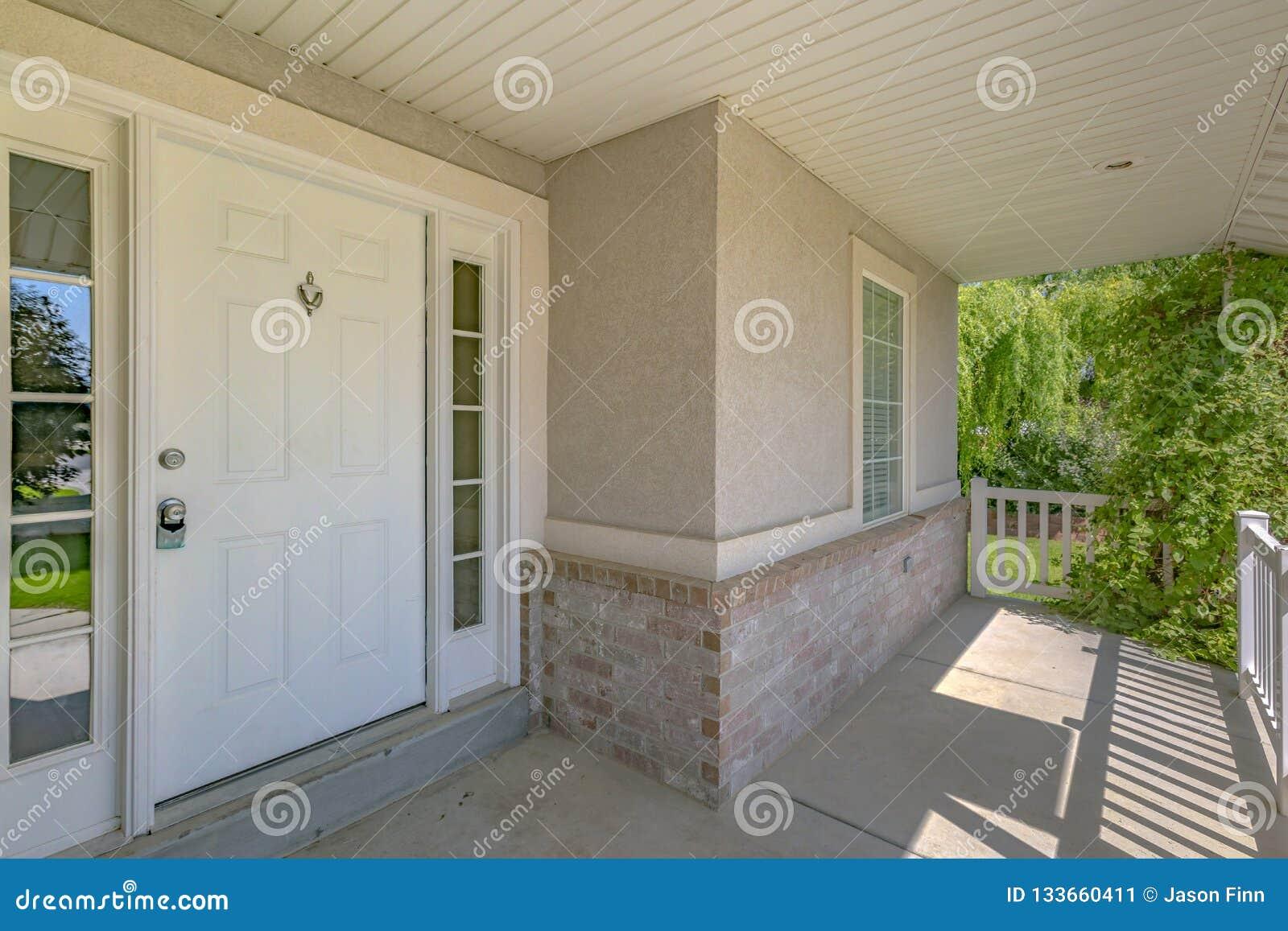 Haus mit weißer Haustür und sonnenbeschienem Portal