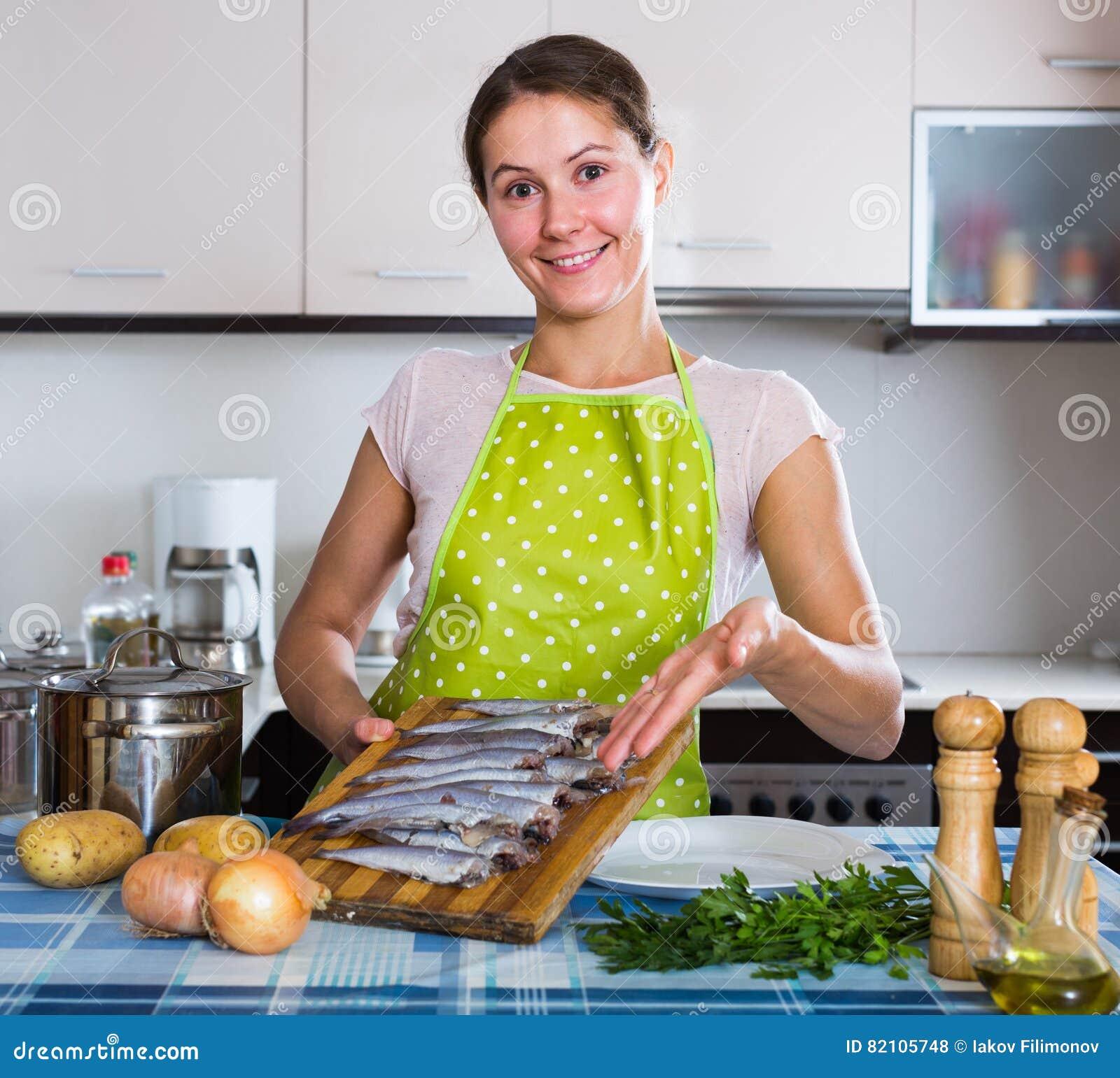 Hausfrau, die neues Rezept von sprattus in der Küche versucht