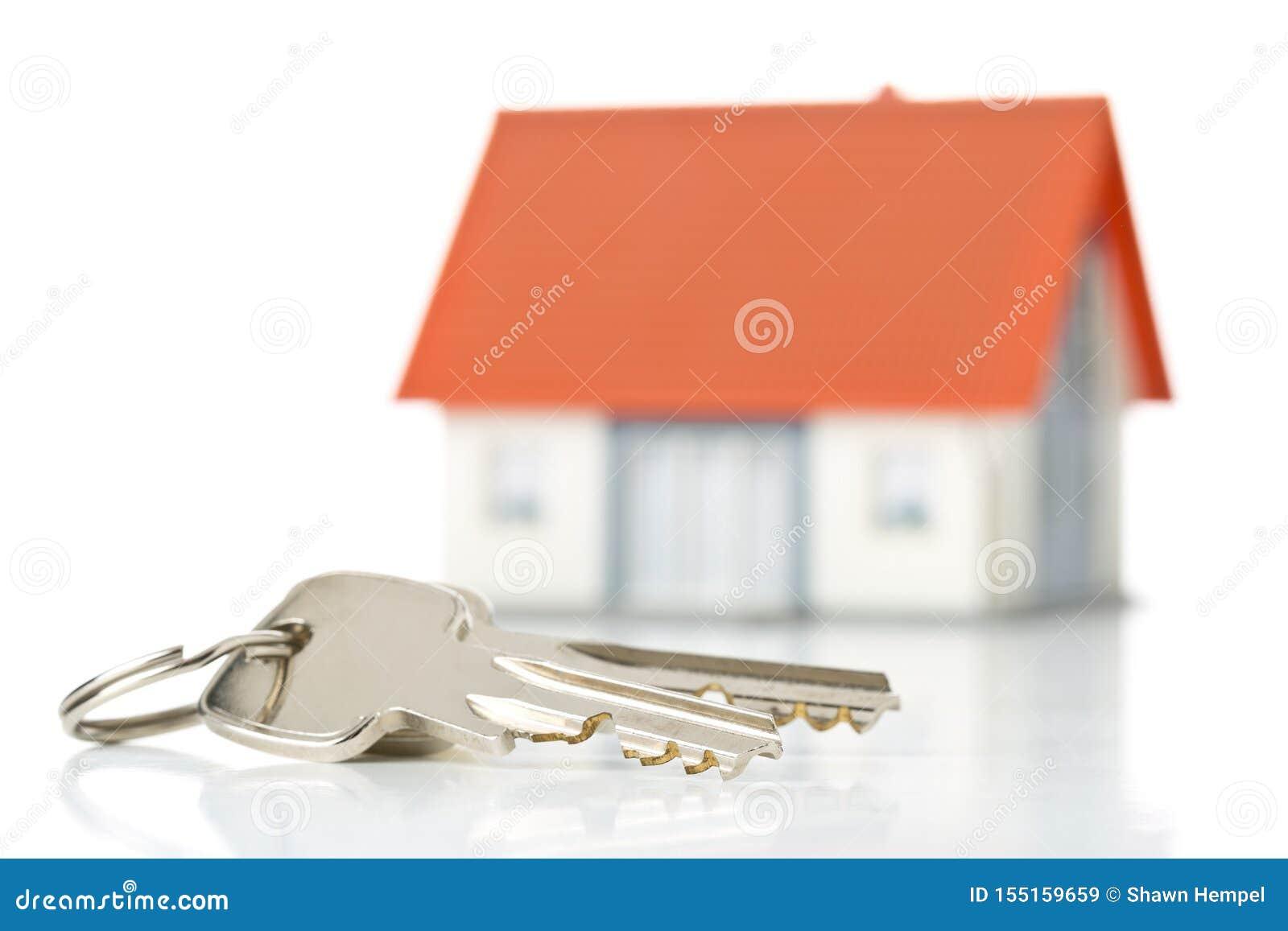 Hausschlüssel vor Musterhaus über weißem Hintergrund - Hauseigentümer, Immobilien oder Wohnungsbaukonzept