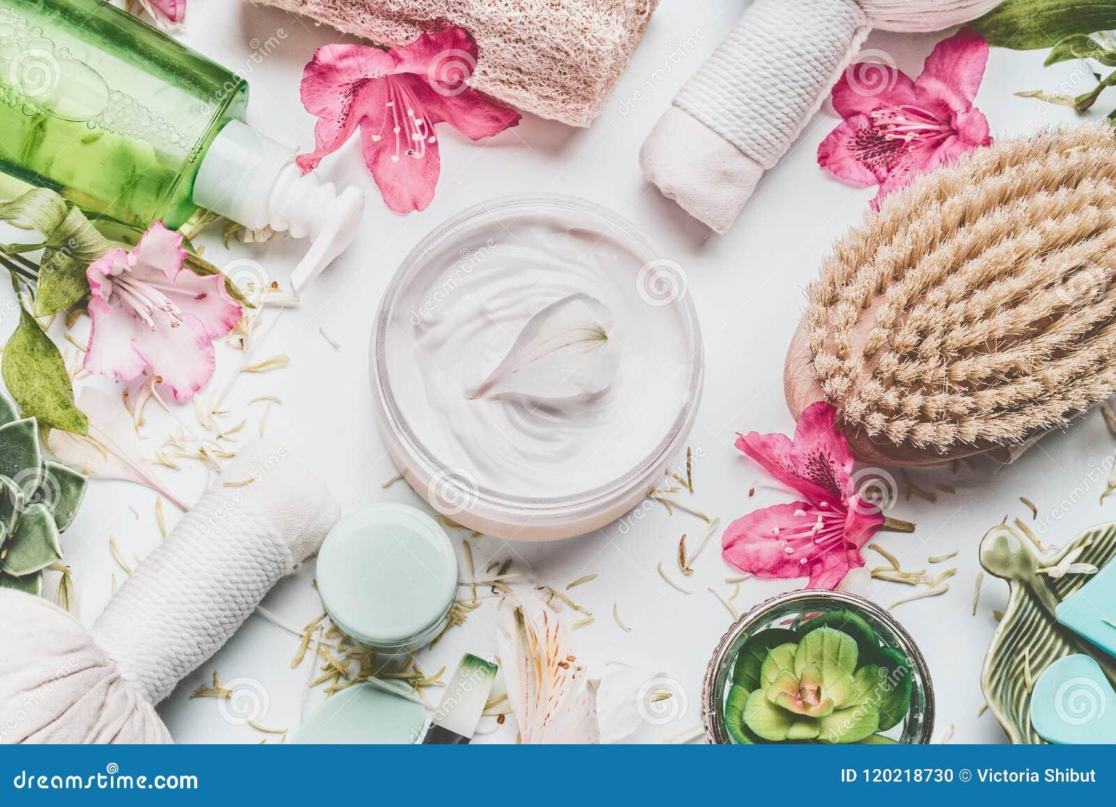 Hautcreme mit den Blumenblumenblättern und -anderen kosmetische Produkte der Körperpflege und Zubehör auf weißem Hintergrund