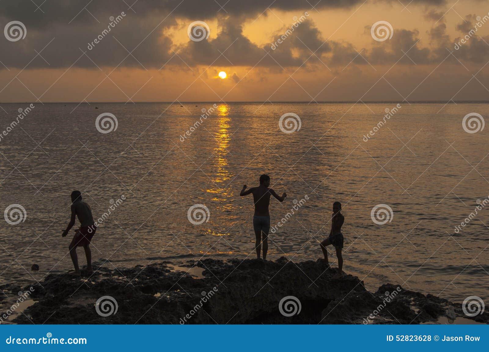 HAVANA/CUBA 2006年7月4日-使用在Malecon的孩子在Sunse