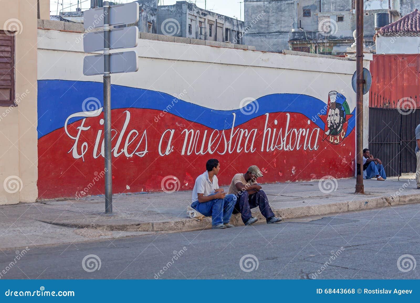 HAVANA, CUBA - APRIL 2, 2012:Cuban teenagers sitting near propaganda graffiti