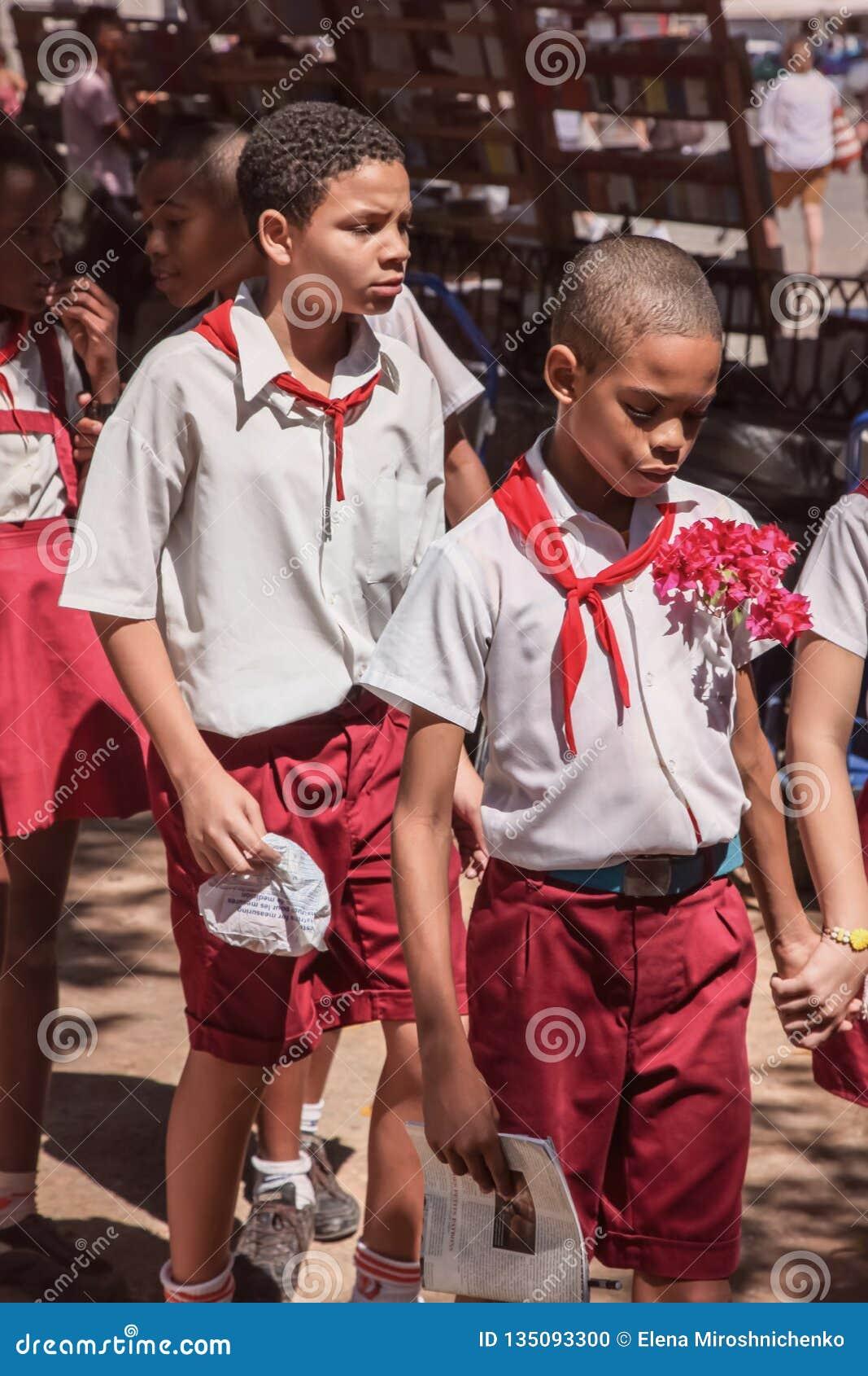 Havana, Cuba - Sept. 2018: De groep leerlingen in eenvormig, twee jongens die samen op de voorzijde gaan