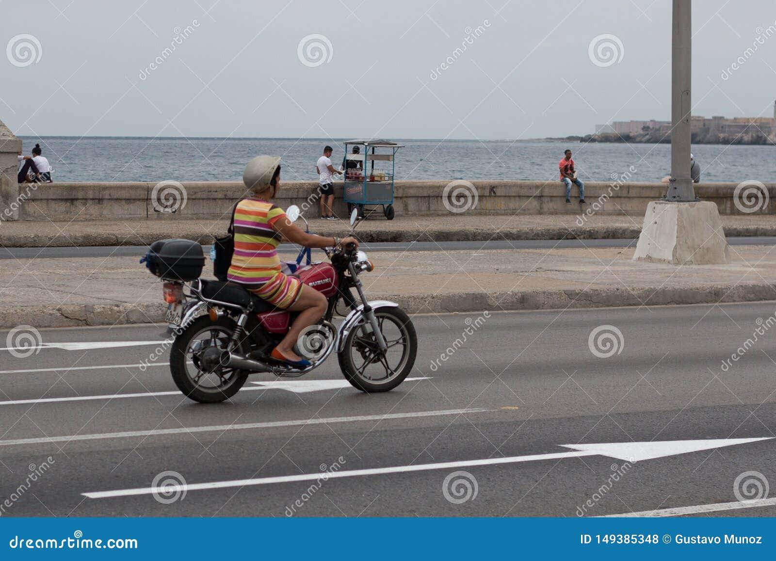 Havana, Kuba - 13. April 2017: Eine Frau f?hrt ein Motorrad entlang dem Malecon in Havana