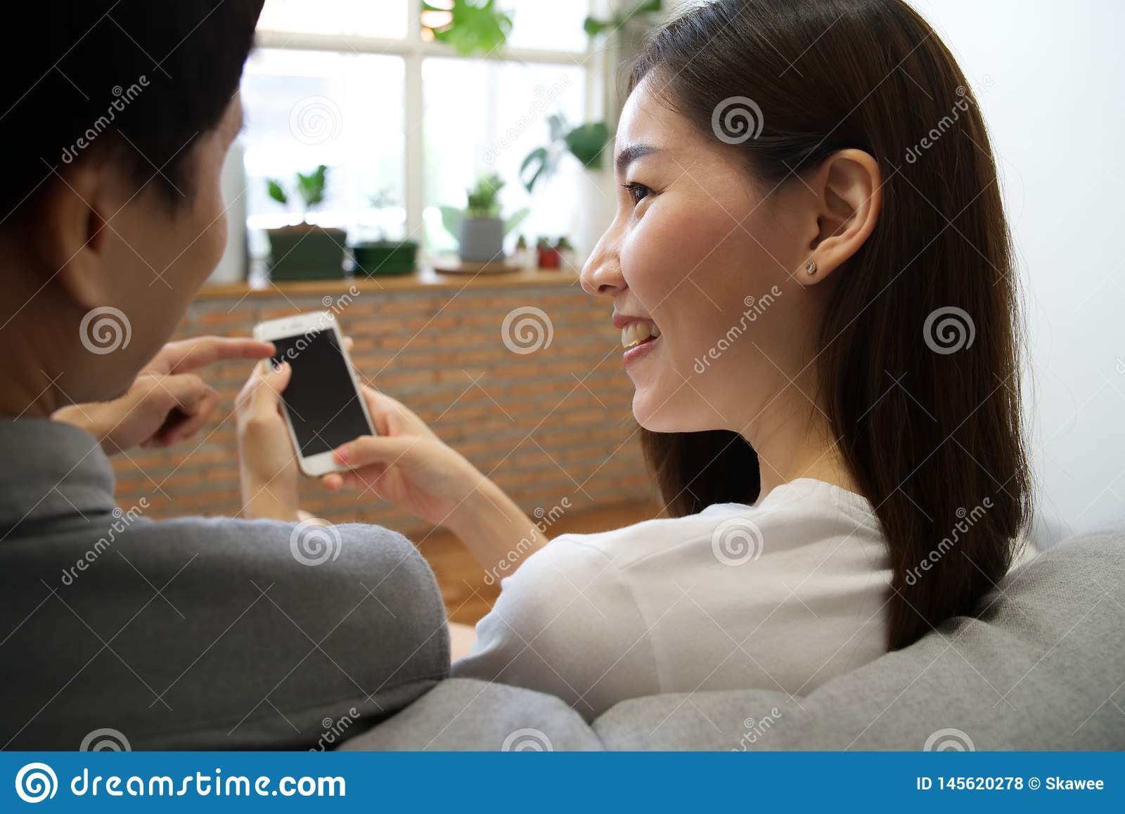 Young Asian couple sitting on sofa are looking at the cellphone.