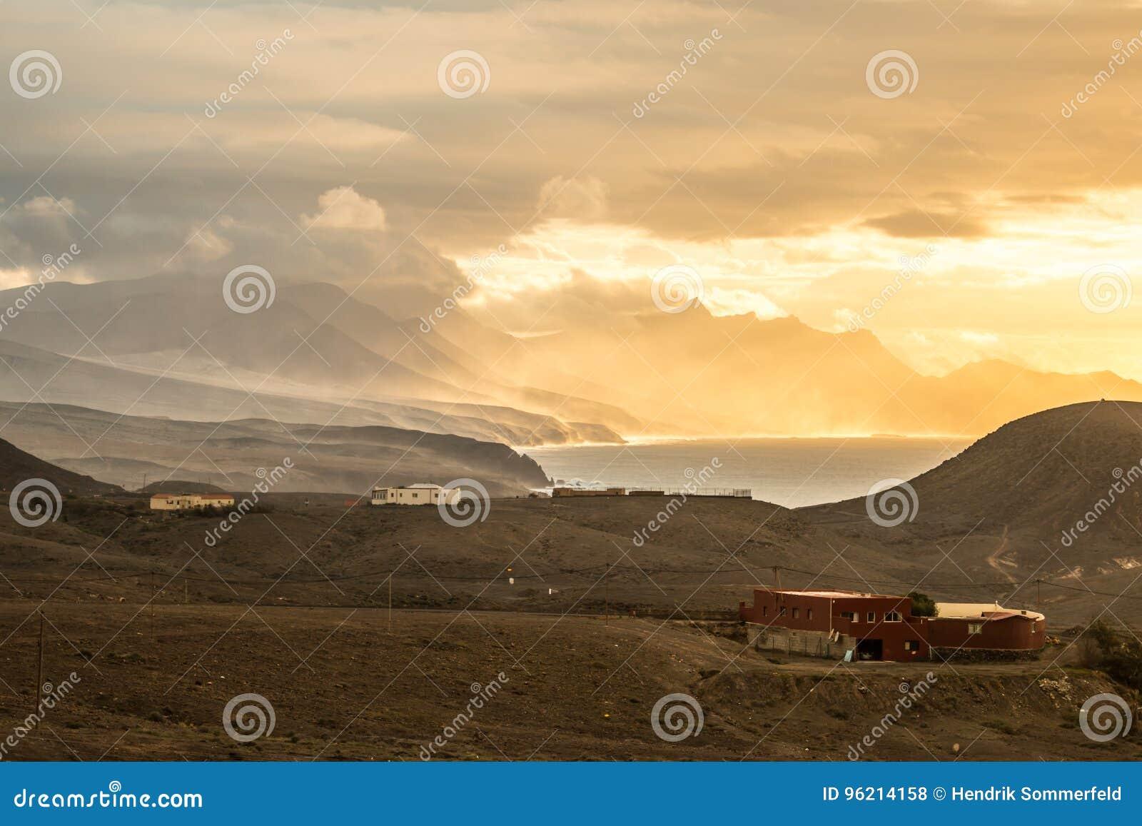 Havsolnedgånglandskap med bergig ljus atmosfär för kustlinje och för epos