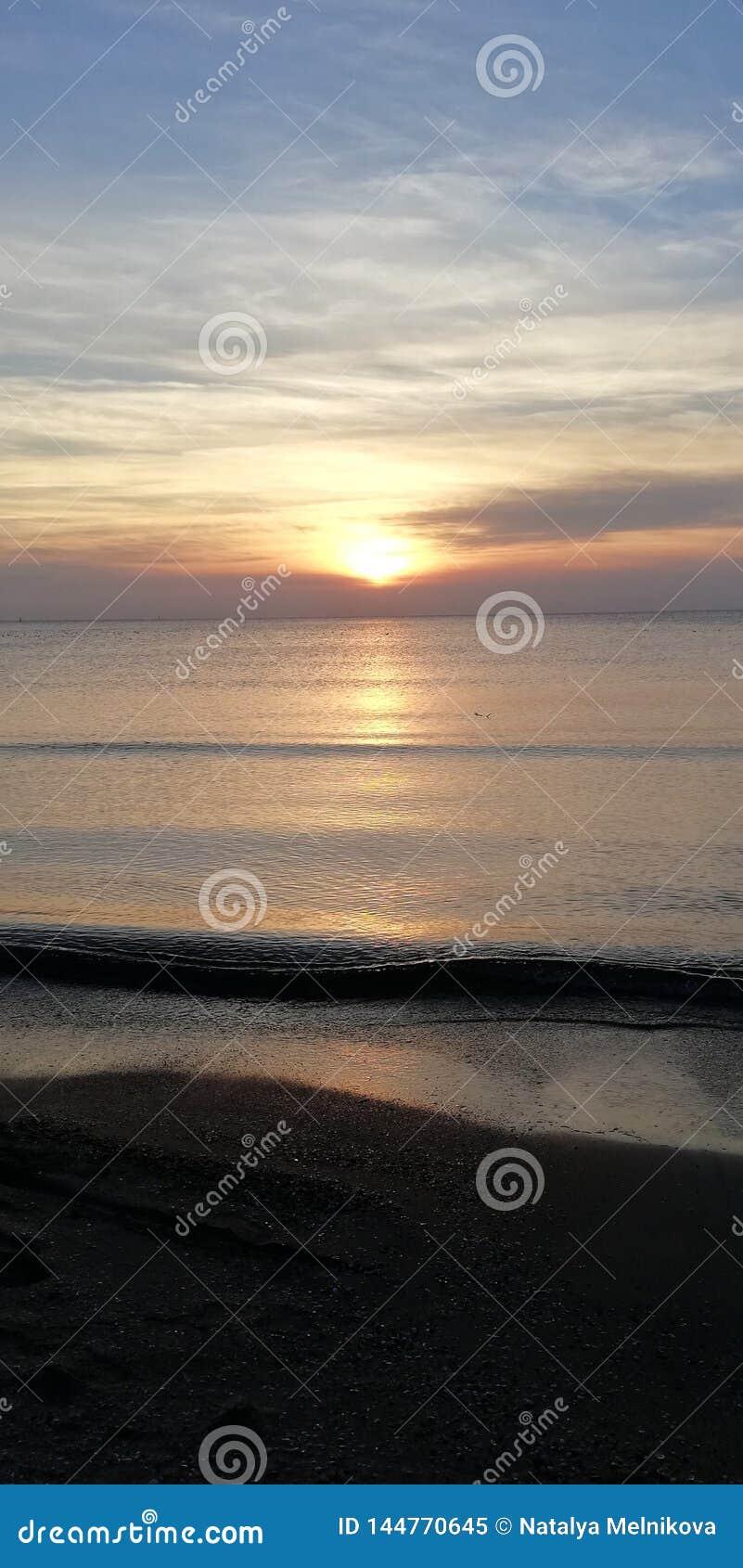 Havssolnedg?ngen landskap Sol- bana p? v?gorna som rullar p? den sandiga stranden