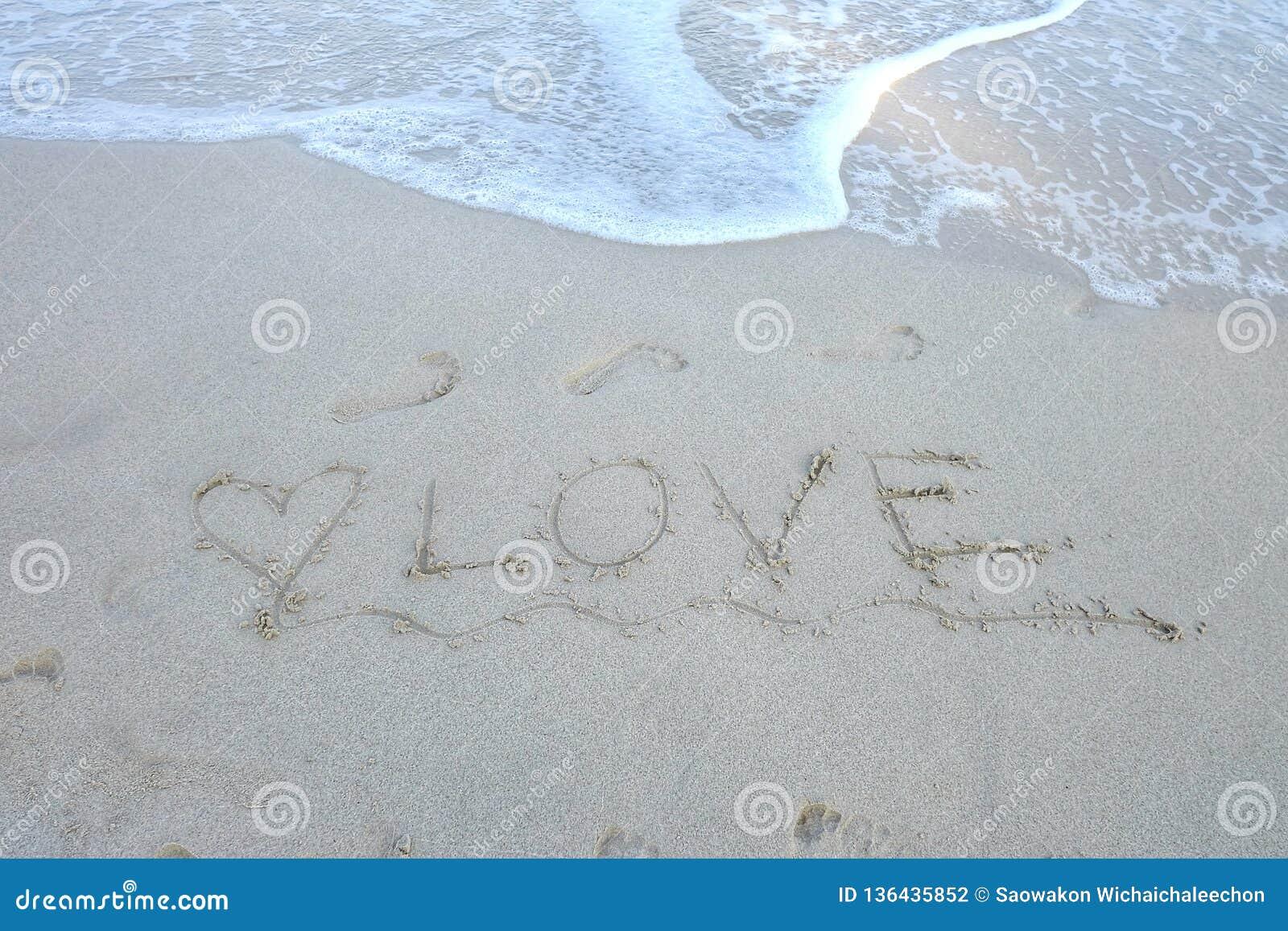 Havsvågor på den rena stranden med ett ord av förälskelse på sanden