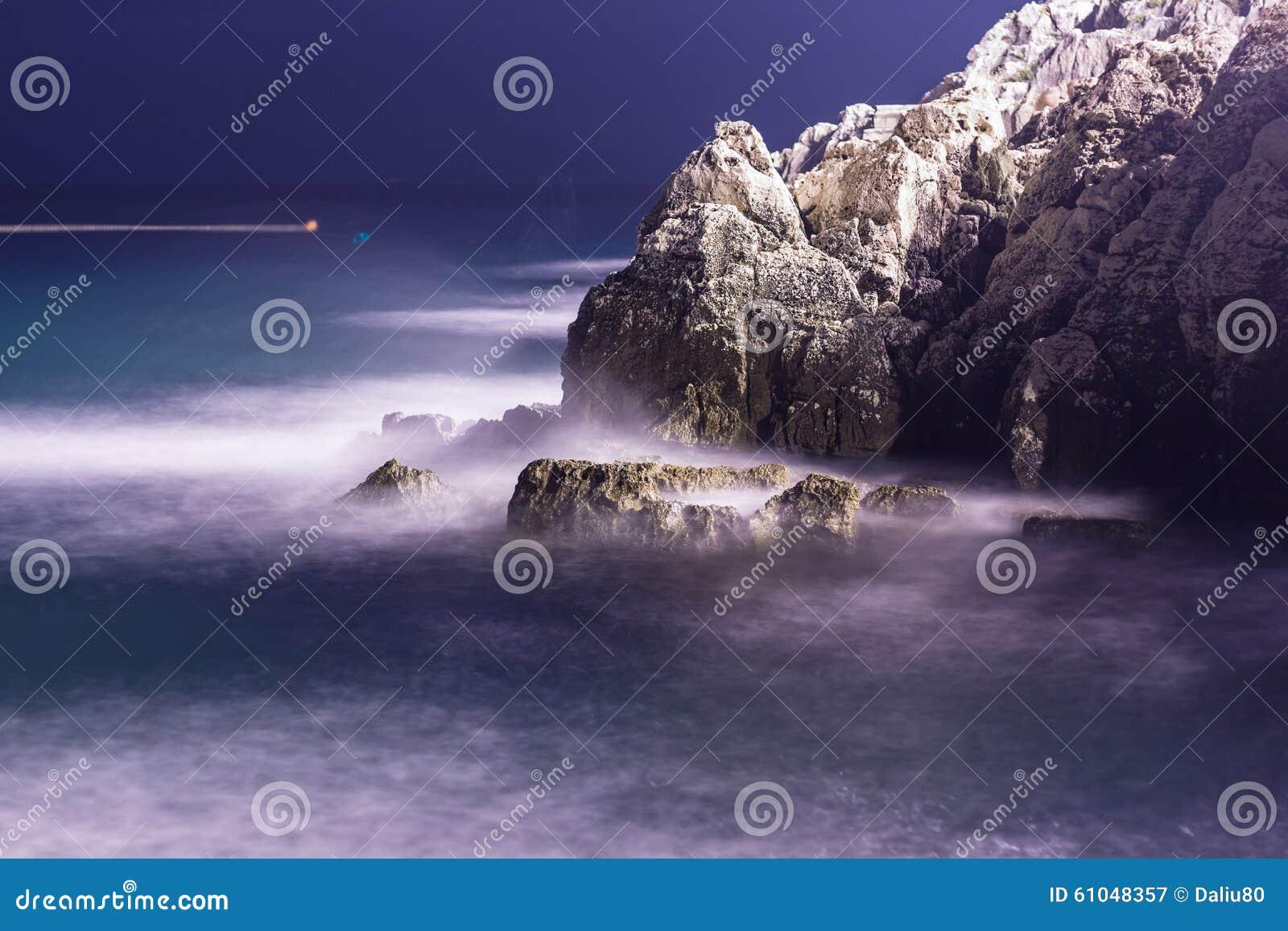 Havsvågor piskar linjen inverkan vaggar på stranden i natt