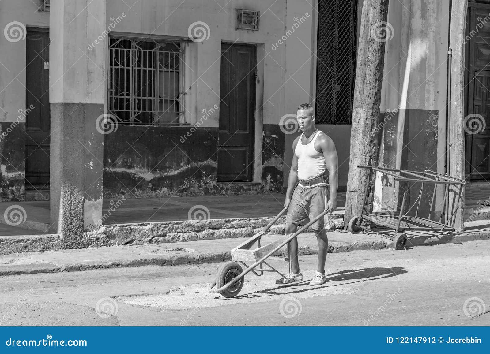 HAWAŃSKI, CUBA-OCTOBER 29 - mężczyzna stacza się staromodny koła taczkowego dla budowy pracy w ulicach Hawański, Oct 29, 2015