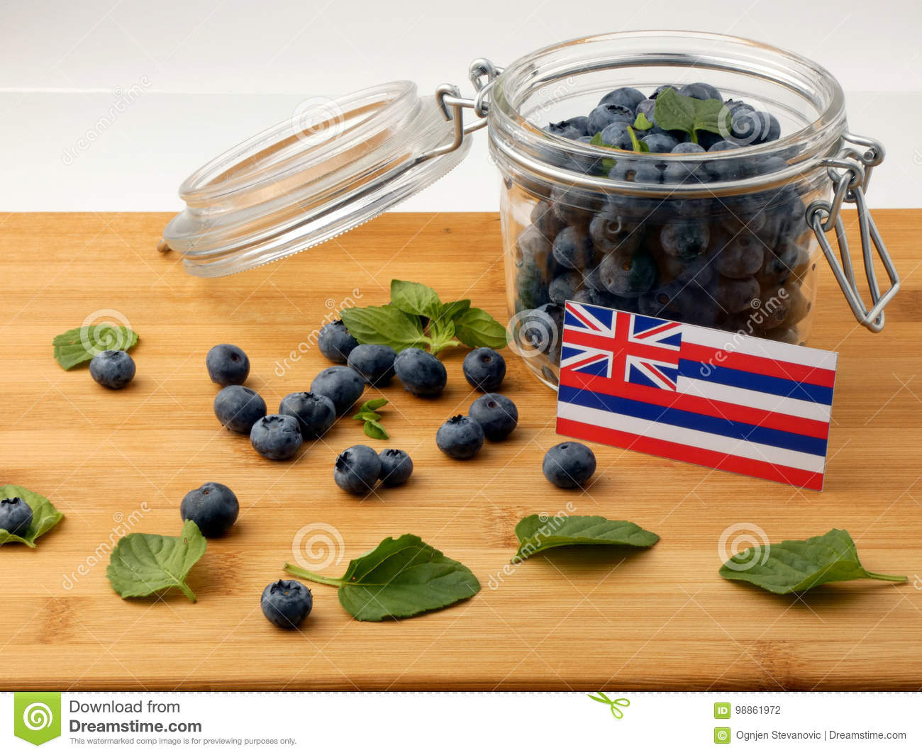 Hawaii flag on a wooden plank with blueberries on white