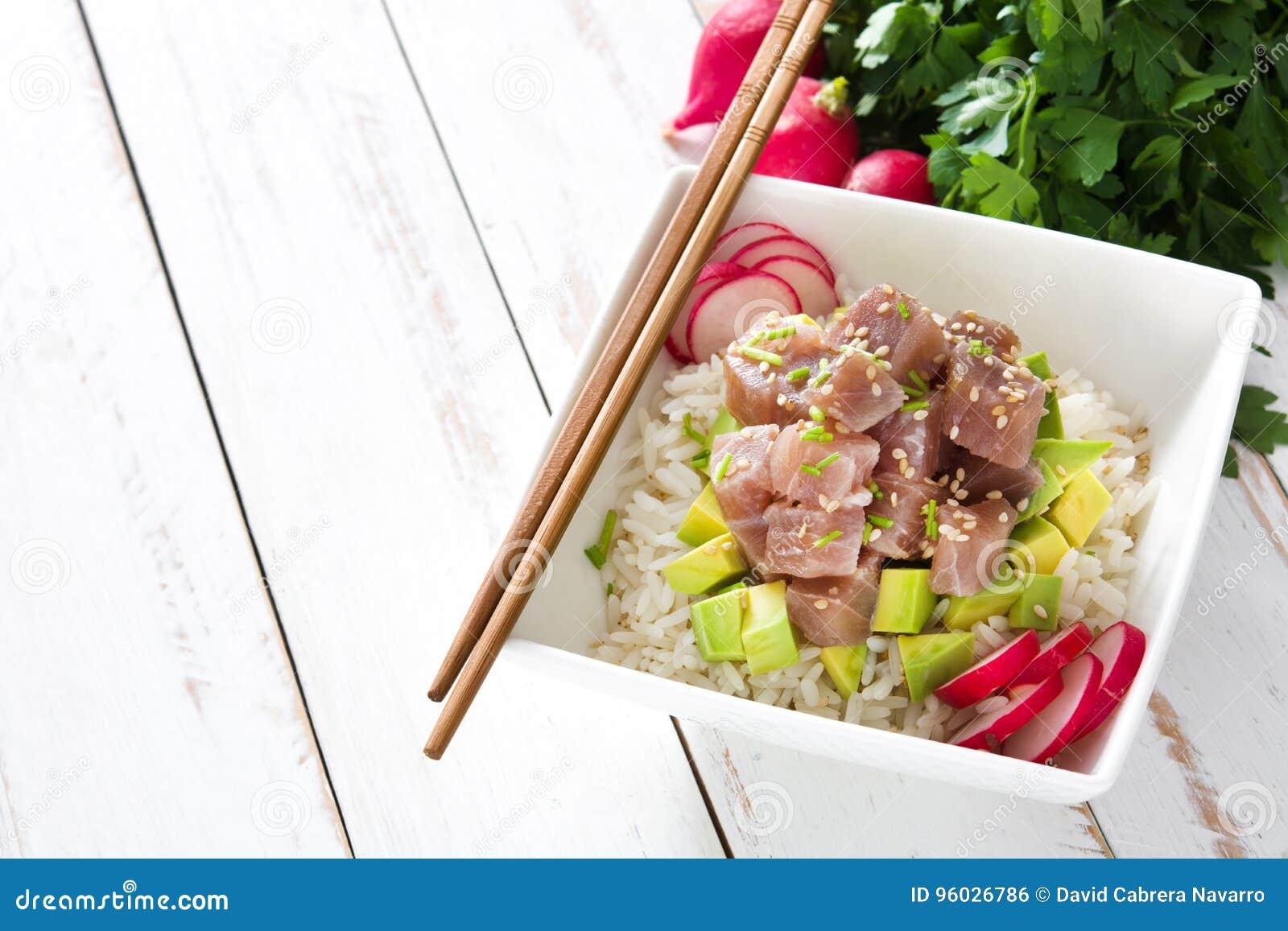 Hawajski tuńczyka potrącenia puchar z avocado, rzodkwiami i sezamowymi ziarnami na drewnie,