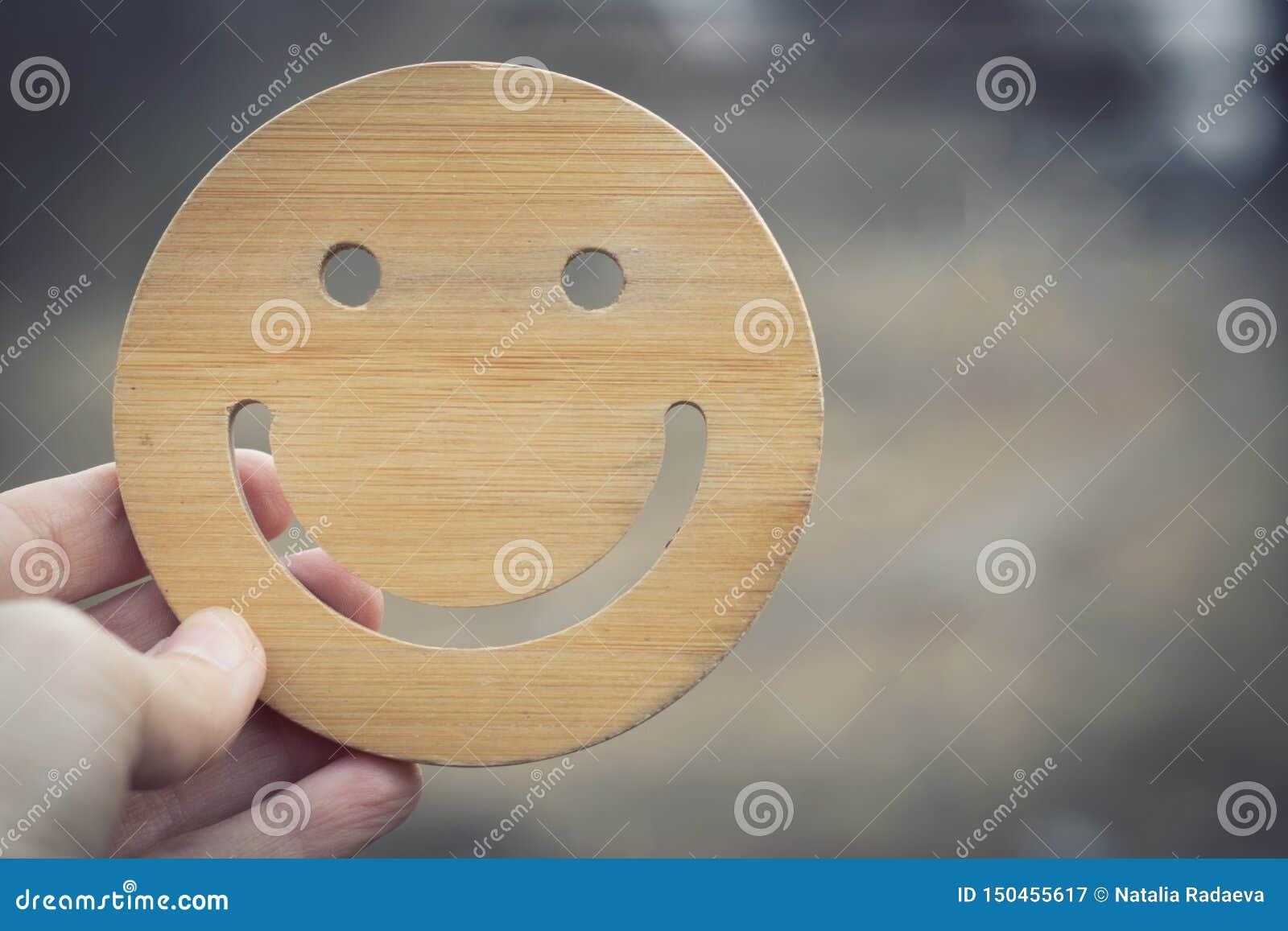 Hay un buen humor cuando hay limpieza y ecología alrededor La mano lleva a cabo el smilie redondo de madera en fondo borroso de l