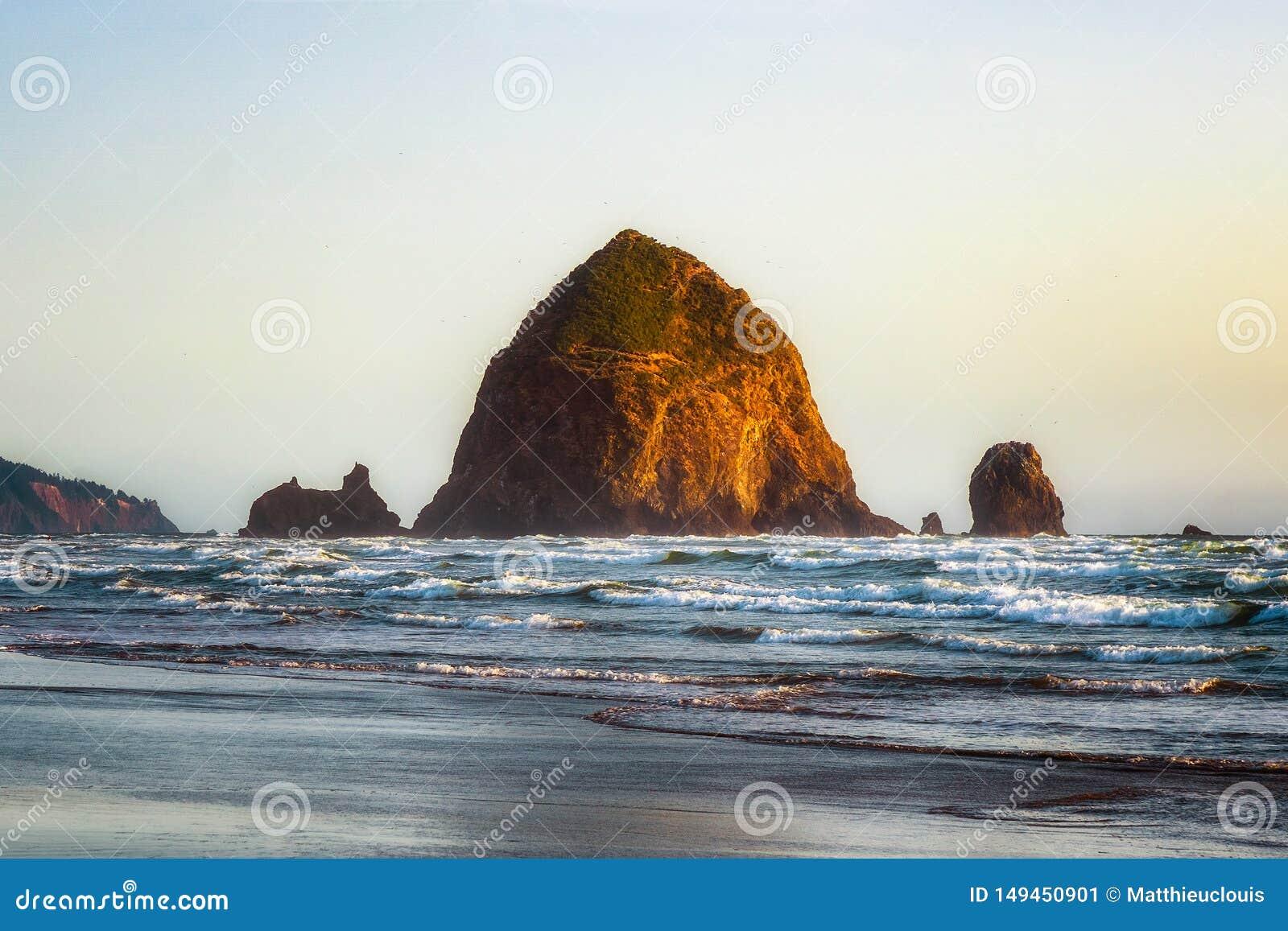 Haystack skały denna sterta przy przypływem przy zmierzchem Naturalny ikonowy punkt zwrotny lokalizować w działo plaży, Oregon wy