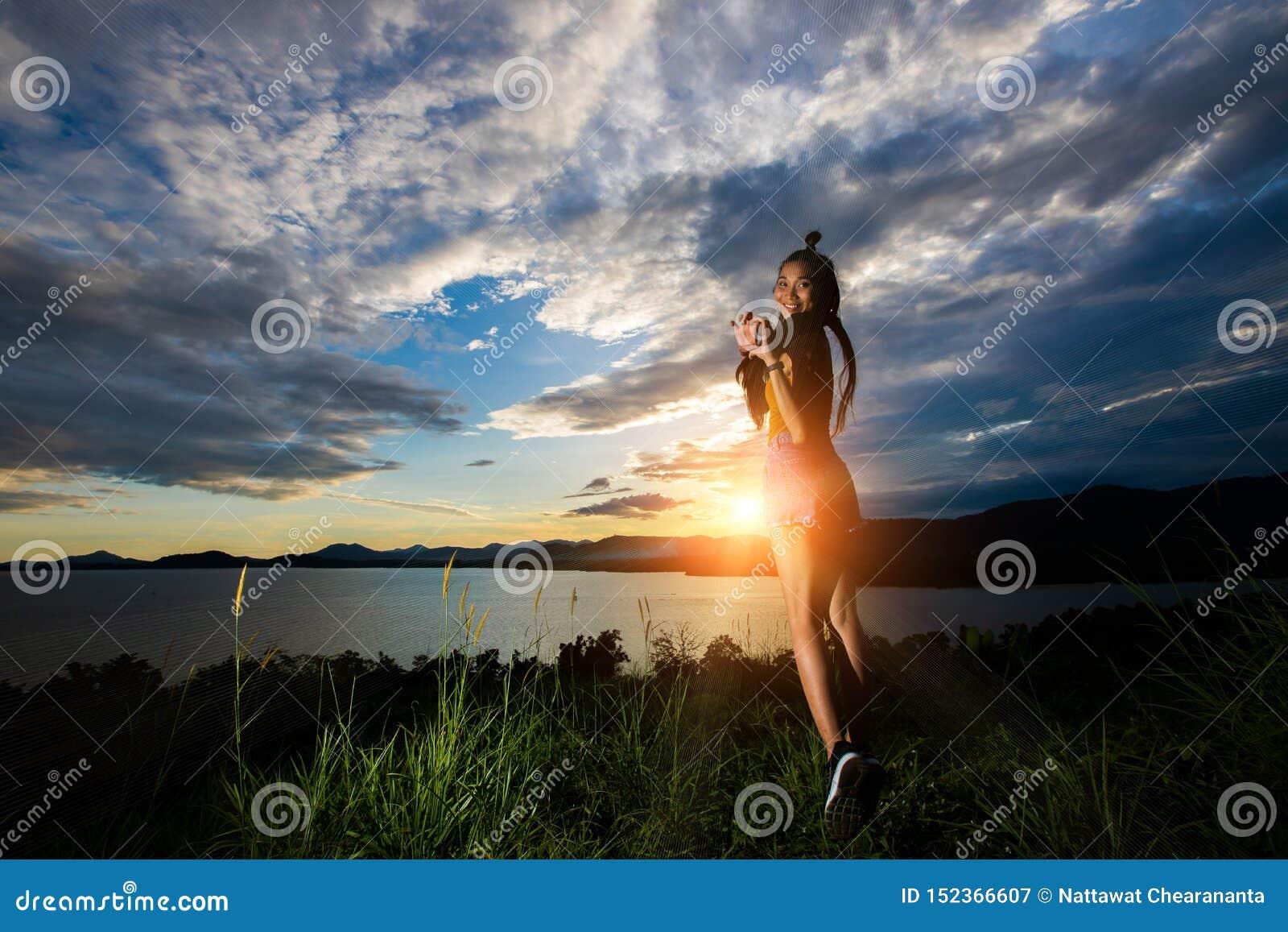 Haz de la nube de la puesta del sol al woma asiático adulto joven