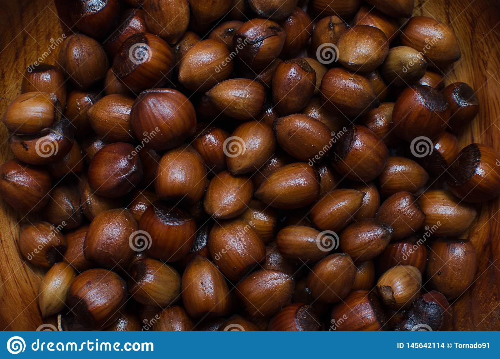 Hazelnuts scattered on boards, photographed from above, forming a uniform background