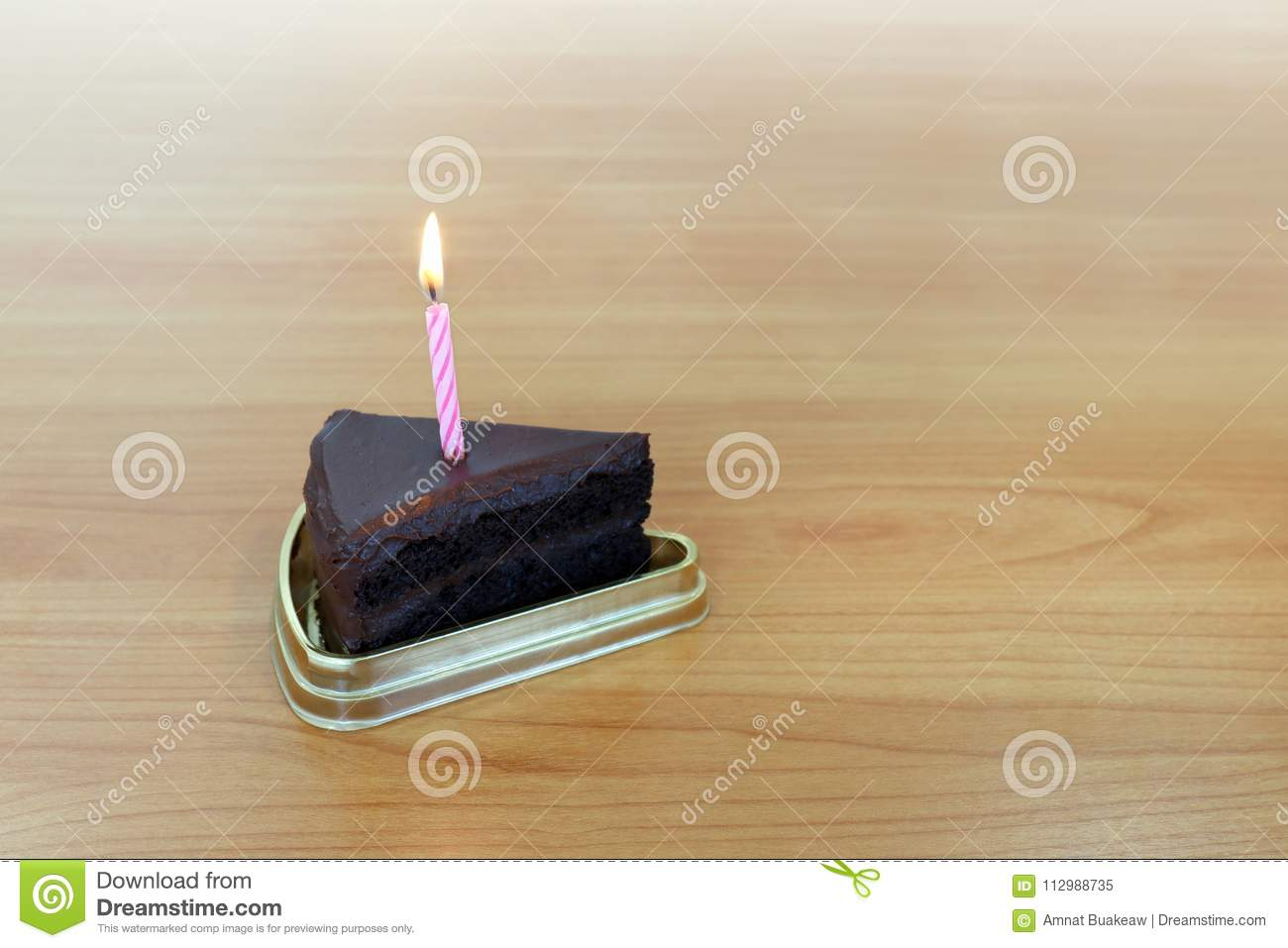 HBD cake Chocolate dark 1 piece crescent, Blowing Cake Candle brown, Happy Birthday one year anniversary on table wood