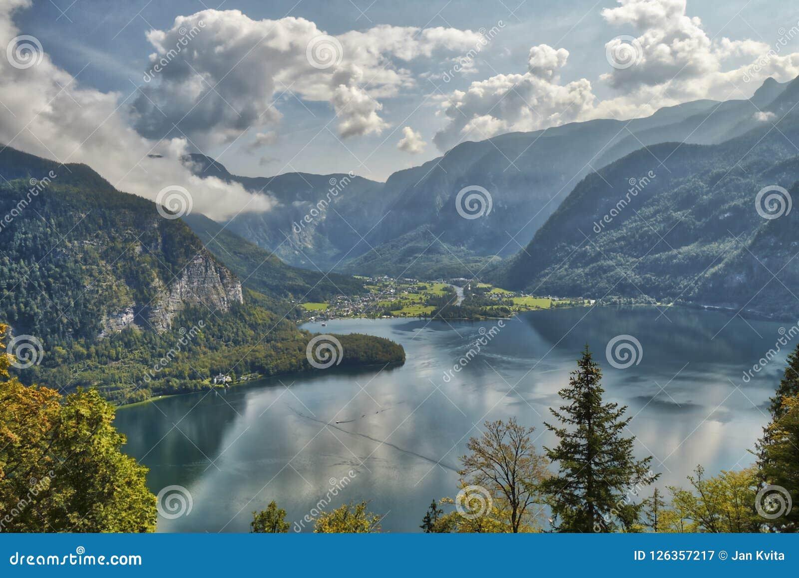 HDR山风景视图与剧烈的多云天空的在Hallstatt村庄附近的一个湖上在奥地利