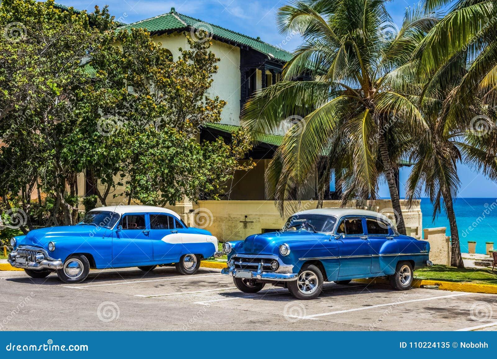 HDR - Αμερικανικά μπλε κλασικά αυτοκίνητα με την άσπρη στέγη που σταθμεύουν στην παραλία κάτω από τους φοίνικες σε Varadero Κούβα